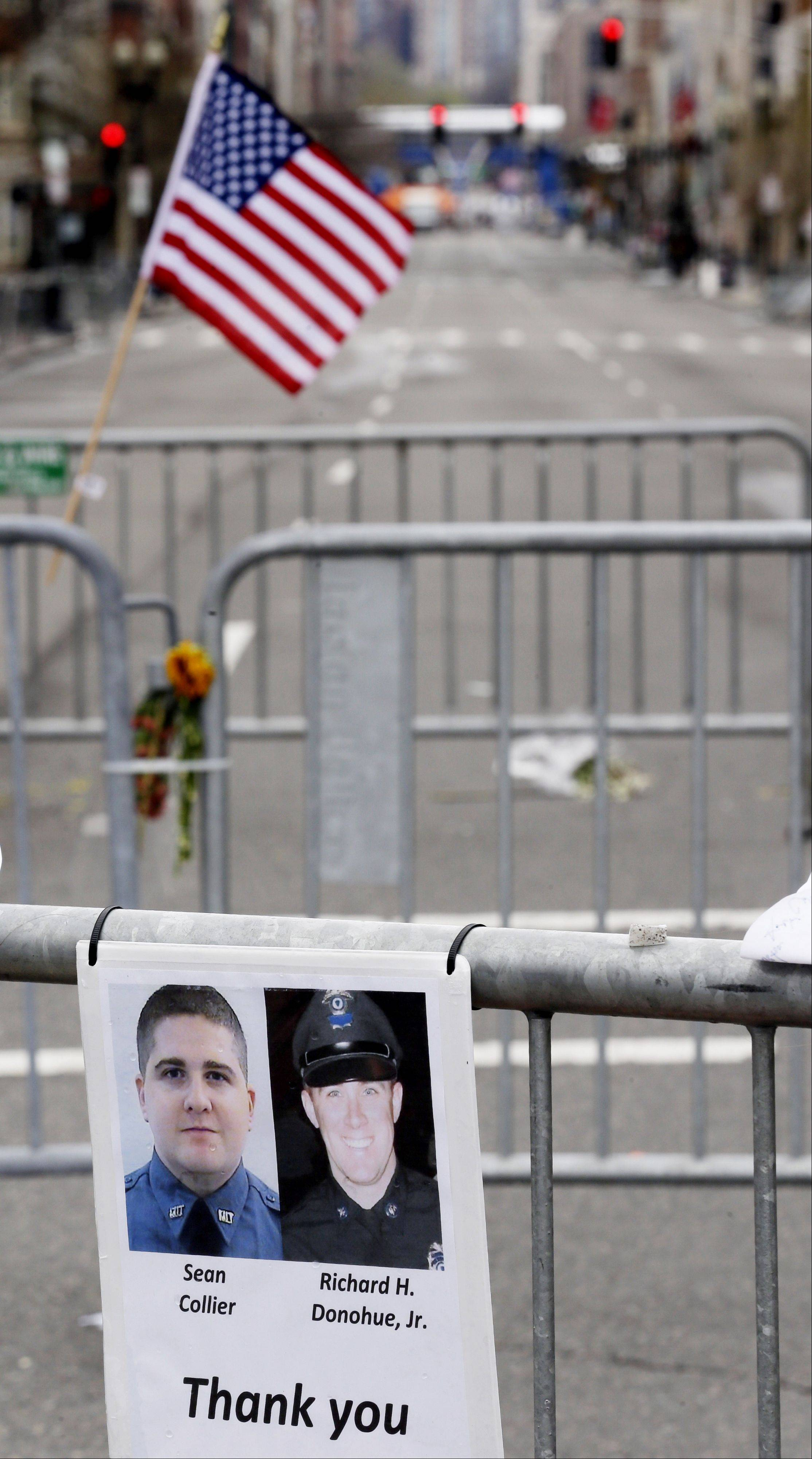 A sign with the photographs of Sean Collier, bottom left, a Massachusetts Institute of Technology officer killed, and Richard Donohue, a Boston Police officer who was shot and critically wounded, is seen at a makeshift memorial on Boylston Street, near the finish line of the Boston Marathon, Saturday.