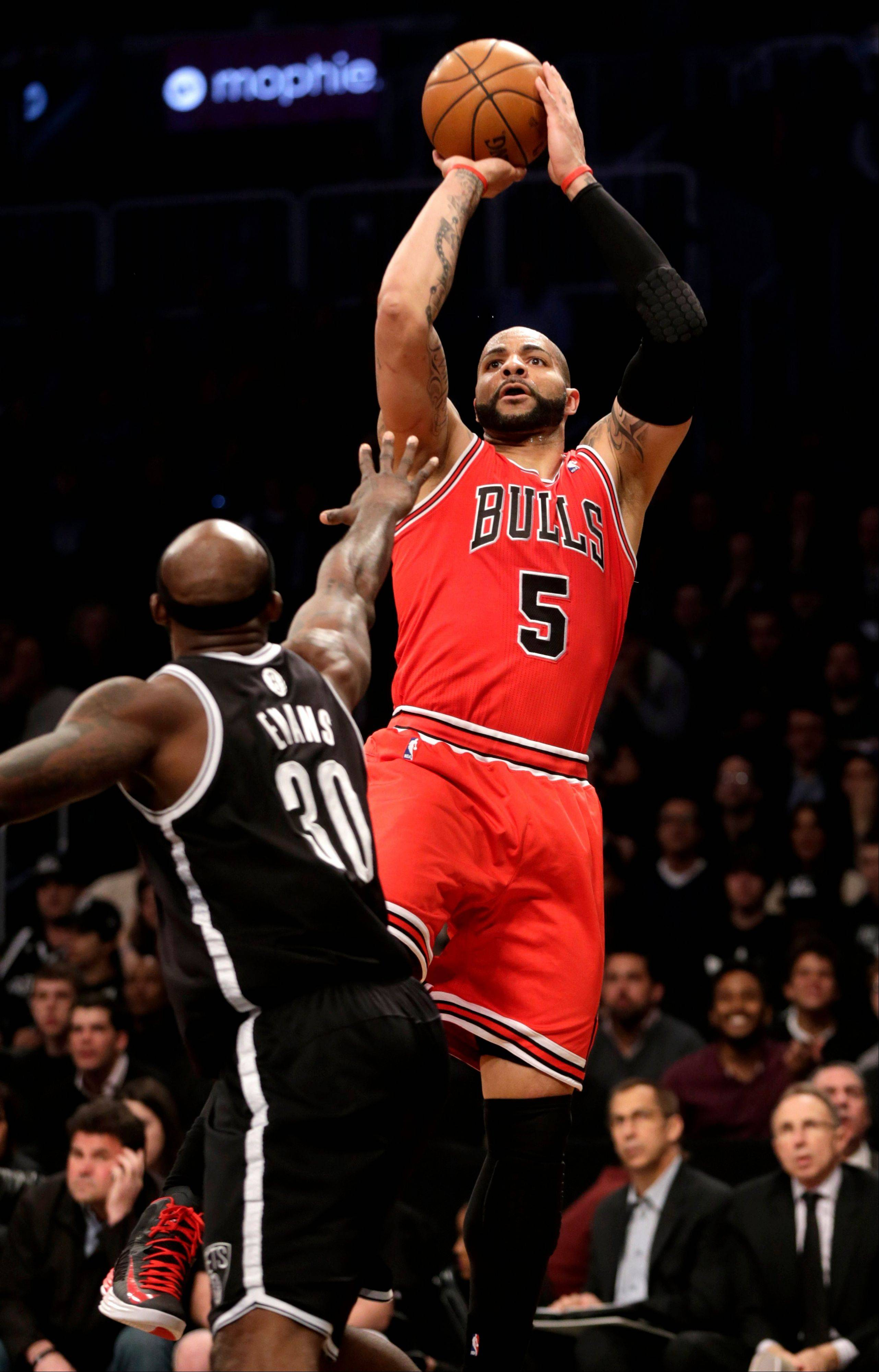 The Carlos Boozer, right, shoots over Brooklyn Nets' Reggie Evans during the first quarter of Game 1 of the first round of the playoffs, Saturday.