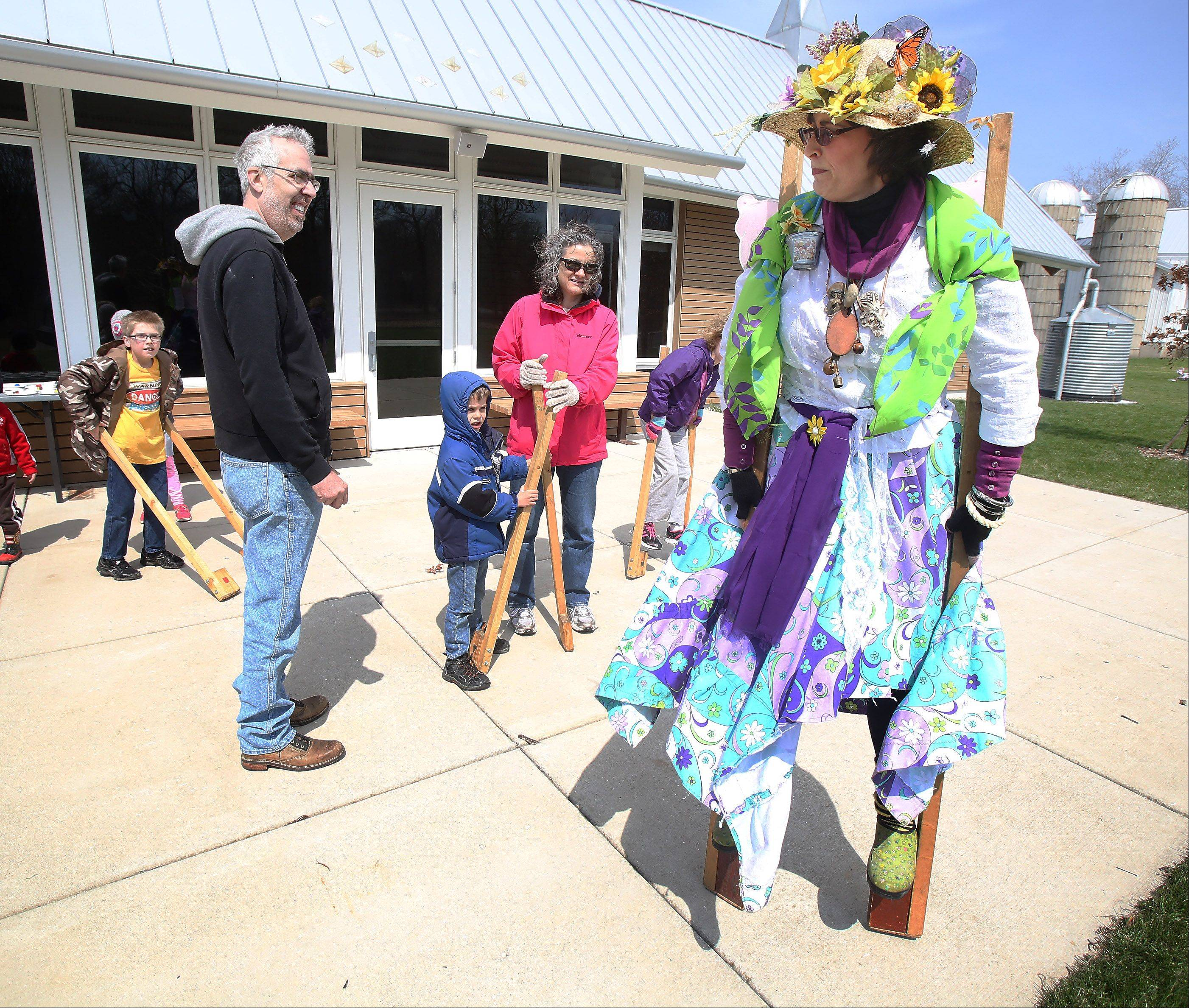 Mother Nature, played by Janice Aull, teaches children how to walk on stilts during the Spring Celebration event Sunday at Ryerson Conservation Area in Riverwoods.