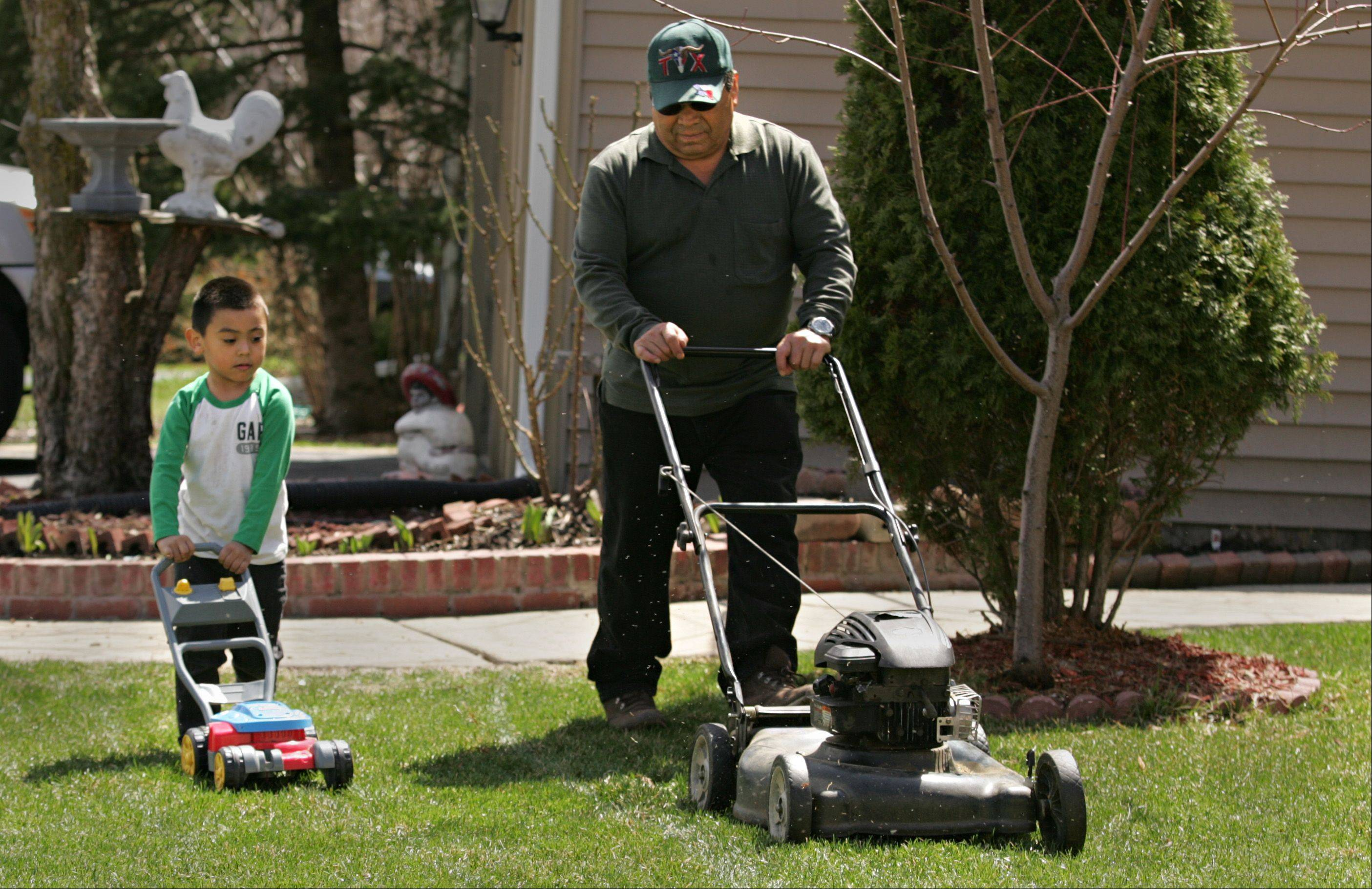 Taking advantage of weather that actually looks and feels like spring, Miguel Bucio and his grandson Angel, 3, mow Miguel's lawn together Tuesday afternoon on Elgin's west side. Angel followed every step alongside his grandfather, practicing for the day when he would run the larger, real thing.