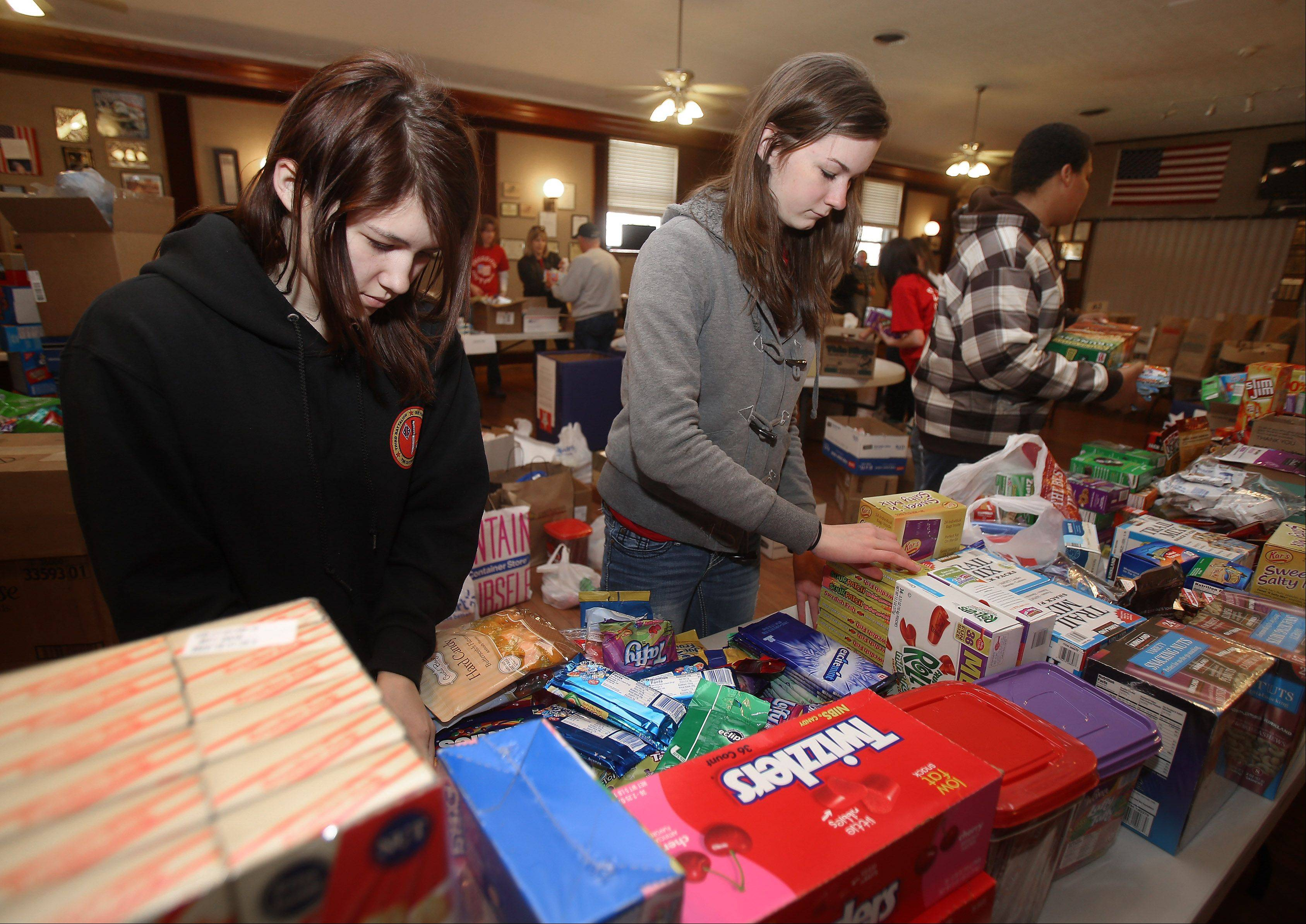 Cousins Joanne Savage, left, and Rebecca Savage, fill boxes during a collection drive for the military overseas Sunday at the Arlington Legion Post 208 in Arlington Heights. The event is organized by the family of LCpl. James B. Stack who was killed in Afghanistan in November 2010.