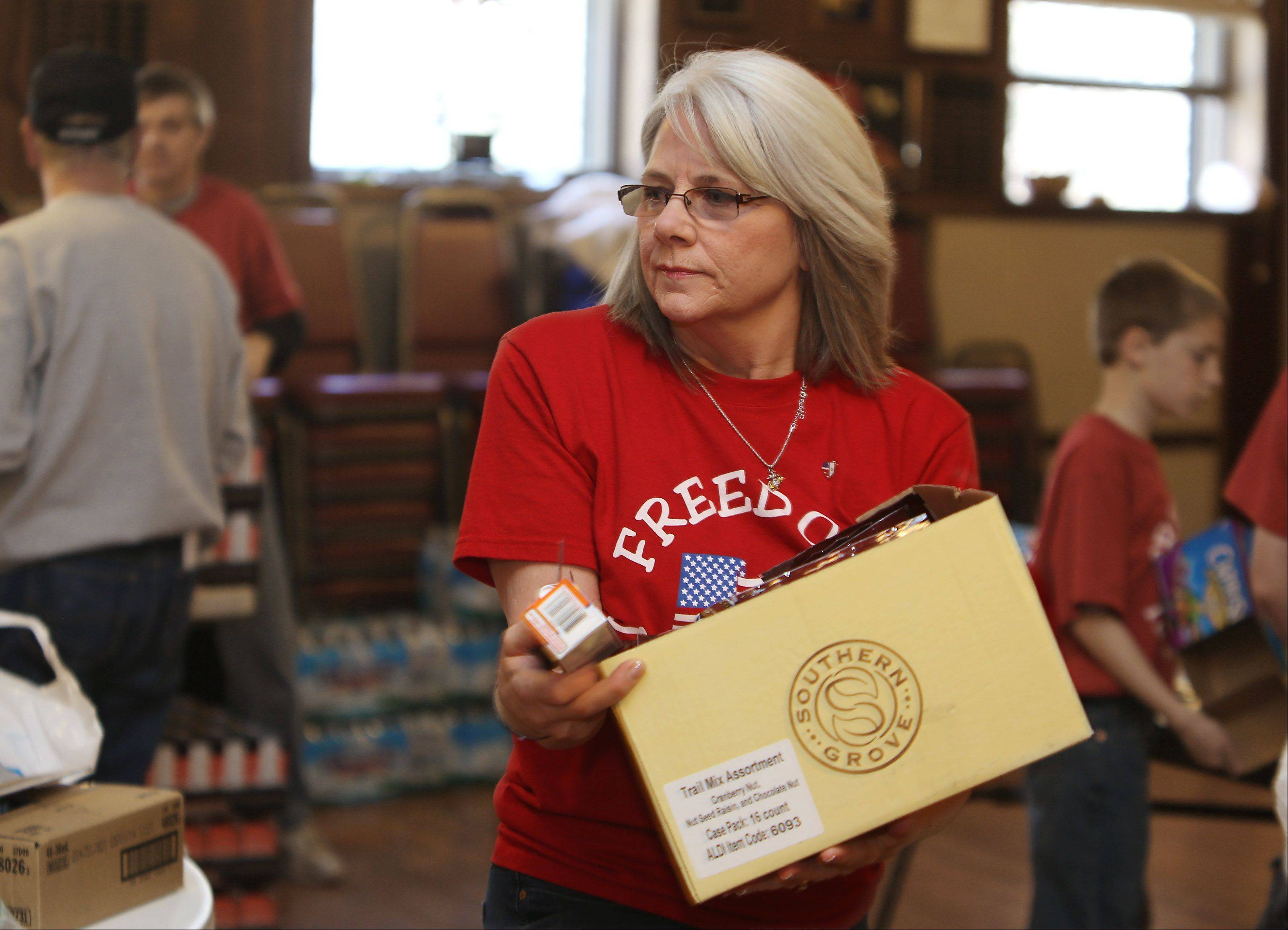Linda Stack, mother of LCpl. James B. Stack, who was killed in Afghanistan in 2011, helps fill boxes during a collection drive for the military overseas Sunday at the Arlington Legion Post 208 in Arlington Heights.