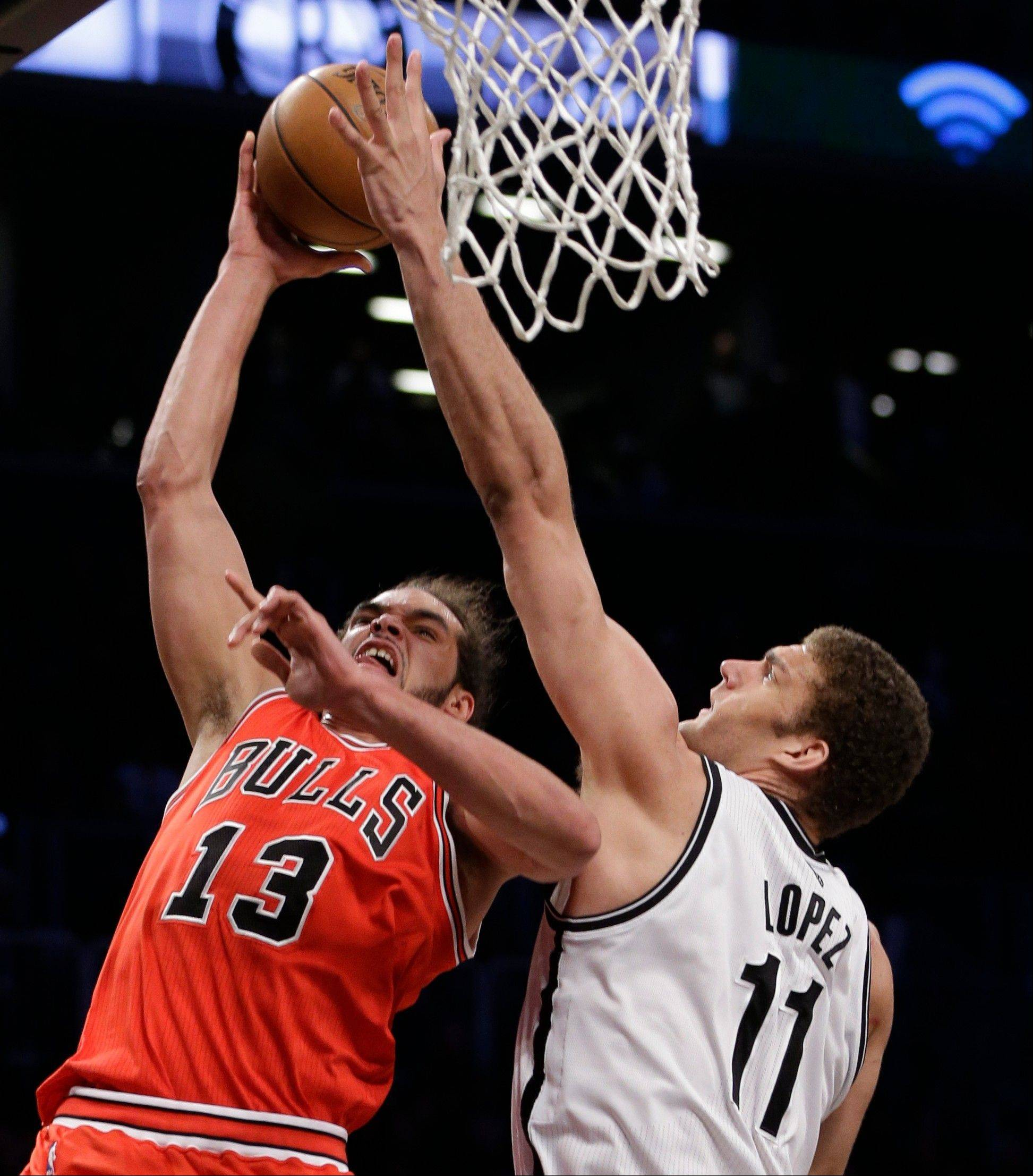 Bulls center Joakim Noah goes strong to the basketball against Nets counterpart Brook Lopez during the second half Monday night.
