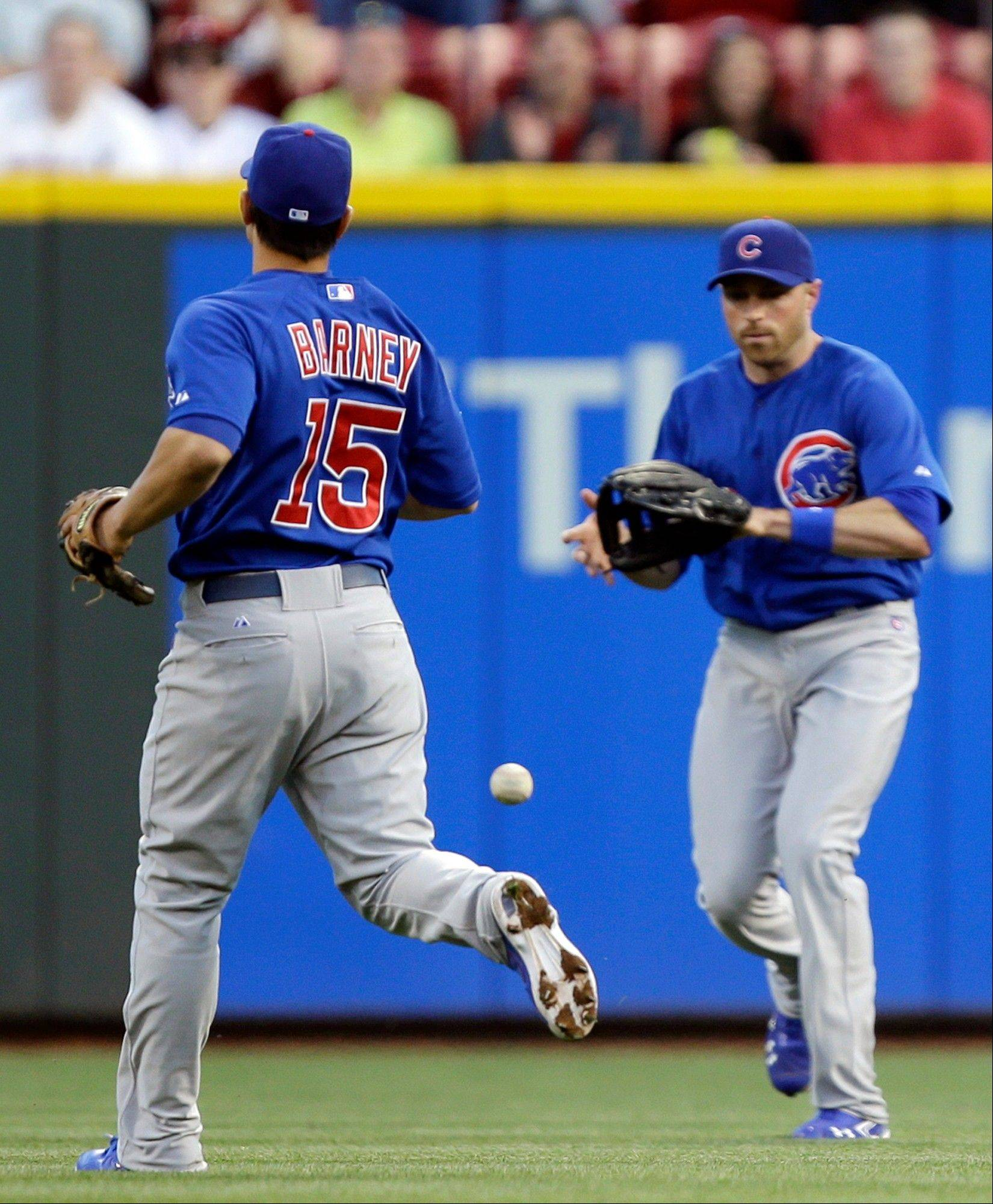 A basehit by the Reds' Devin Mesoraco falls between Cubs second baseman Darwin Barney and right fielder Nate Schierholtz in the third inning Mondayin Cincinnati.