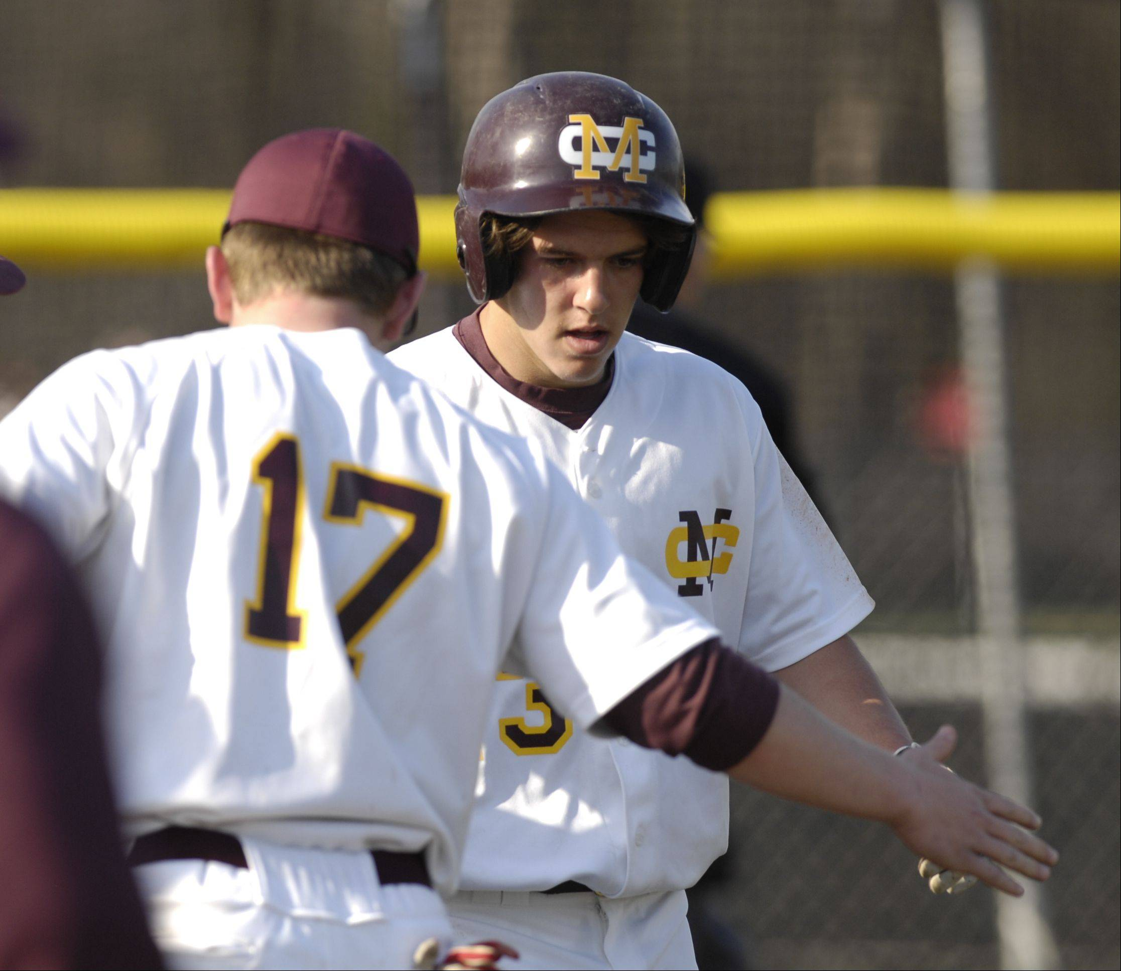 Jake Mencacci and Tyler Tumpane of Montini celebrate Tumpane's score in during first inning against St. Francis boys varsity baseball at home, Monday.