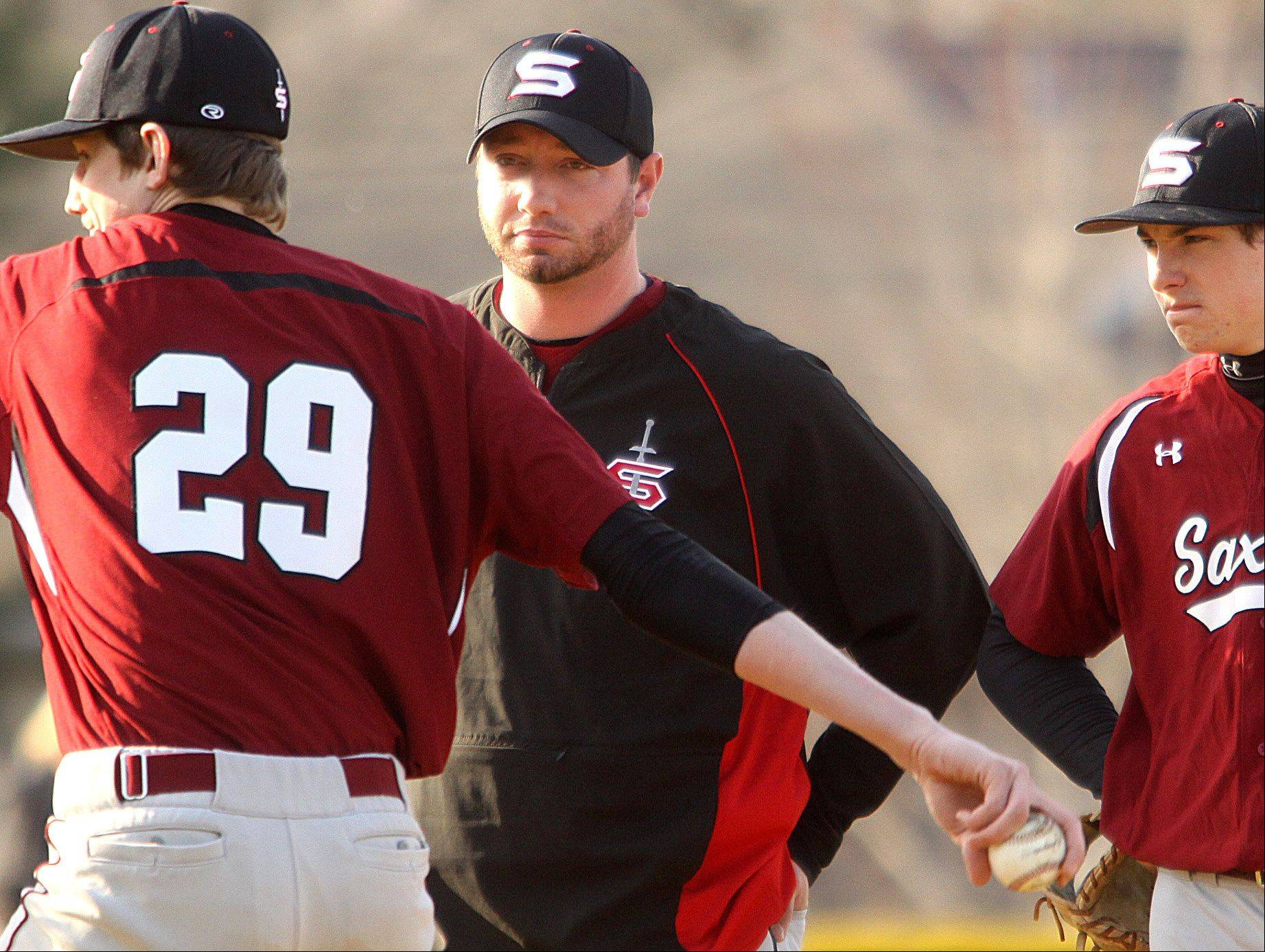 Schaumburg coach Cal Seely, center, monitors warm-up activity of reliever Jon Flynn against Fremd in Palatine on Monday.