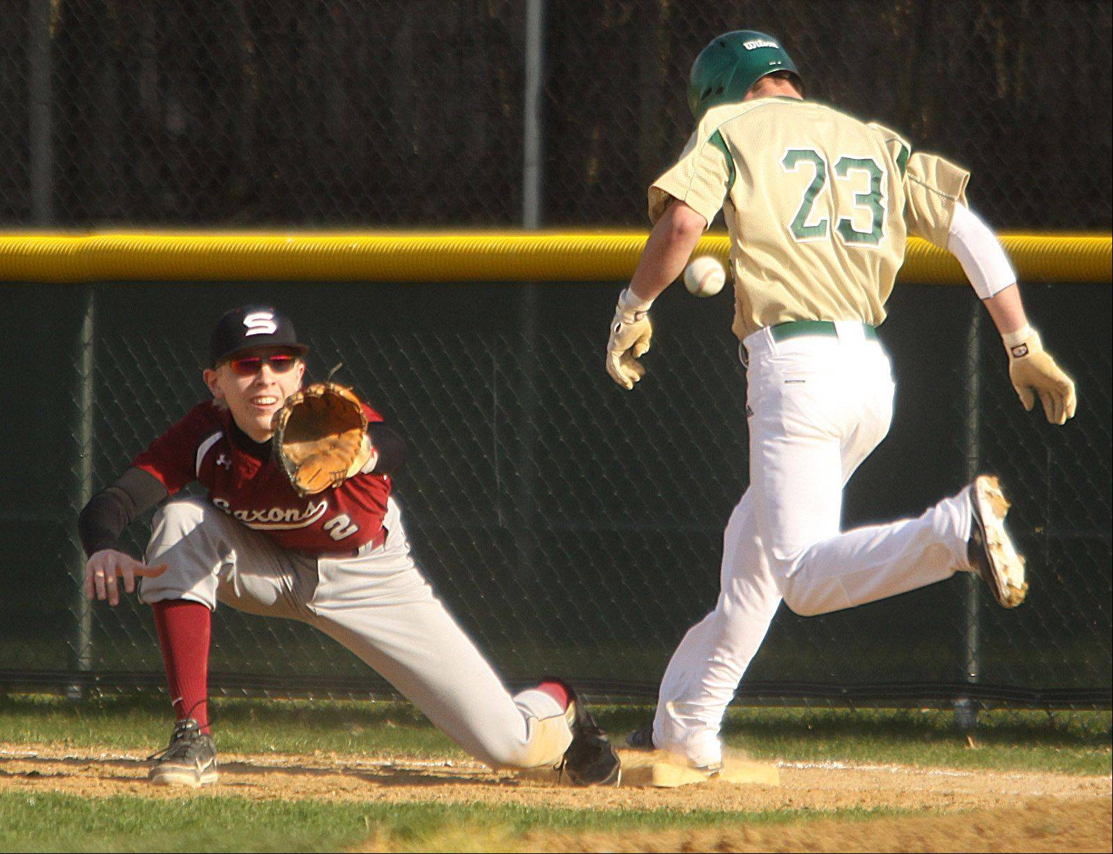 Fremd's Matt Isola, right, is safe at first just ahead of the ball received by Schaumburg first baseman Joe Petritis in Palatine on Monday.