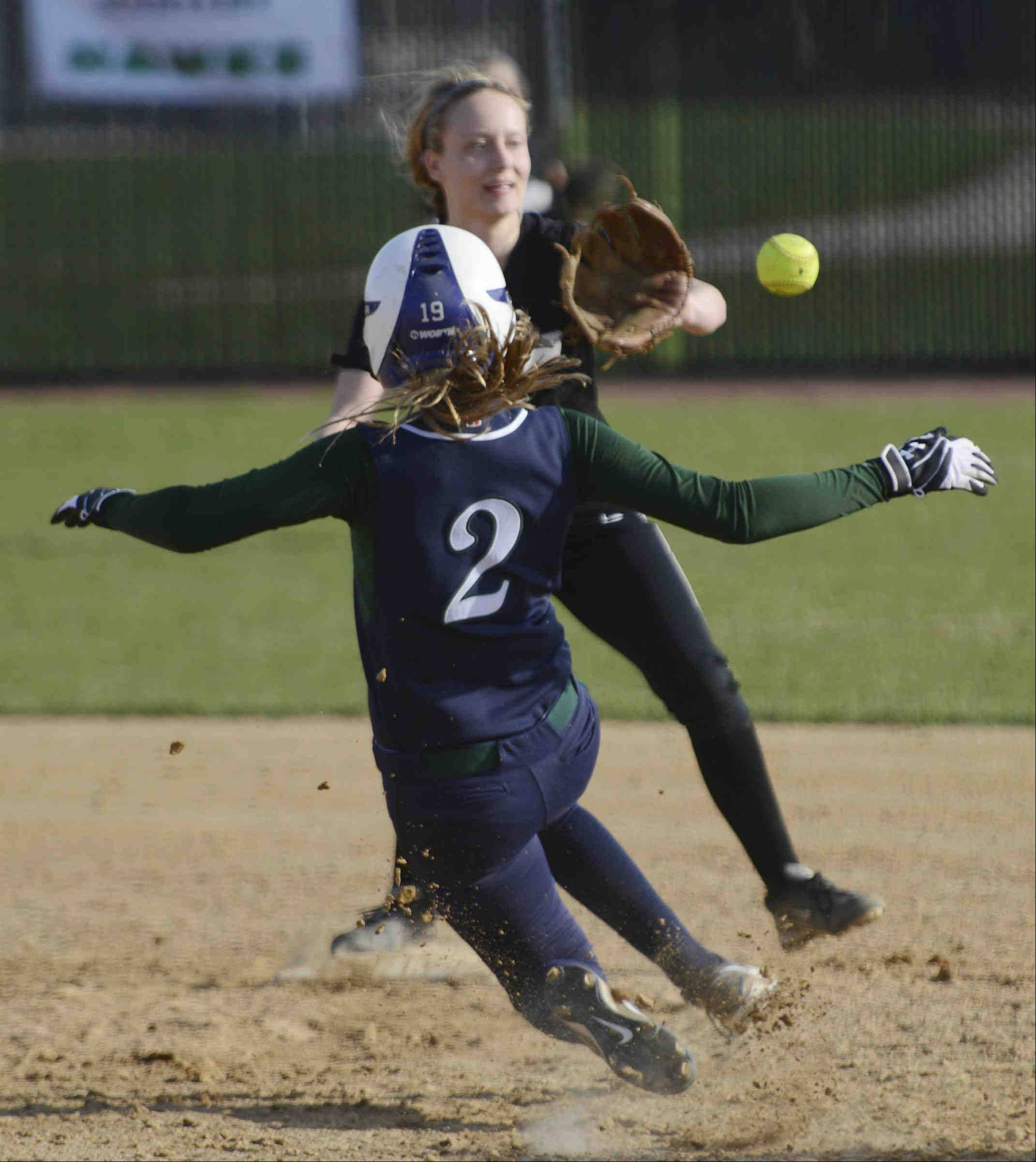 Bartlett's Kathryn Fornoff tries to break up a double play as St. Charles North shortstop Mickey Goetz takes the throw from second baseman Kaitlyn Waslawski Monday in St. Charles. Goetz could not make the throw and Kayla Haberstich was safe at first in the fifth inning.