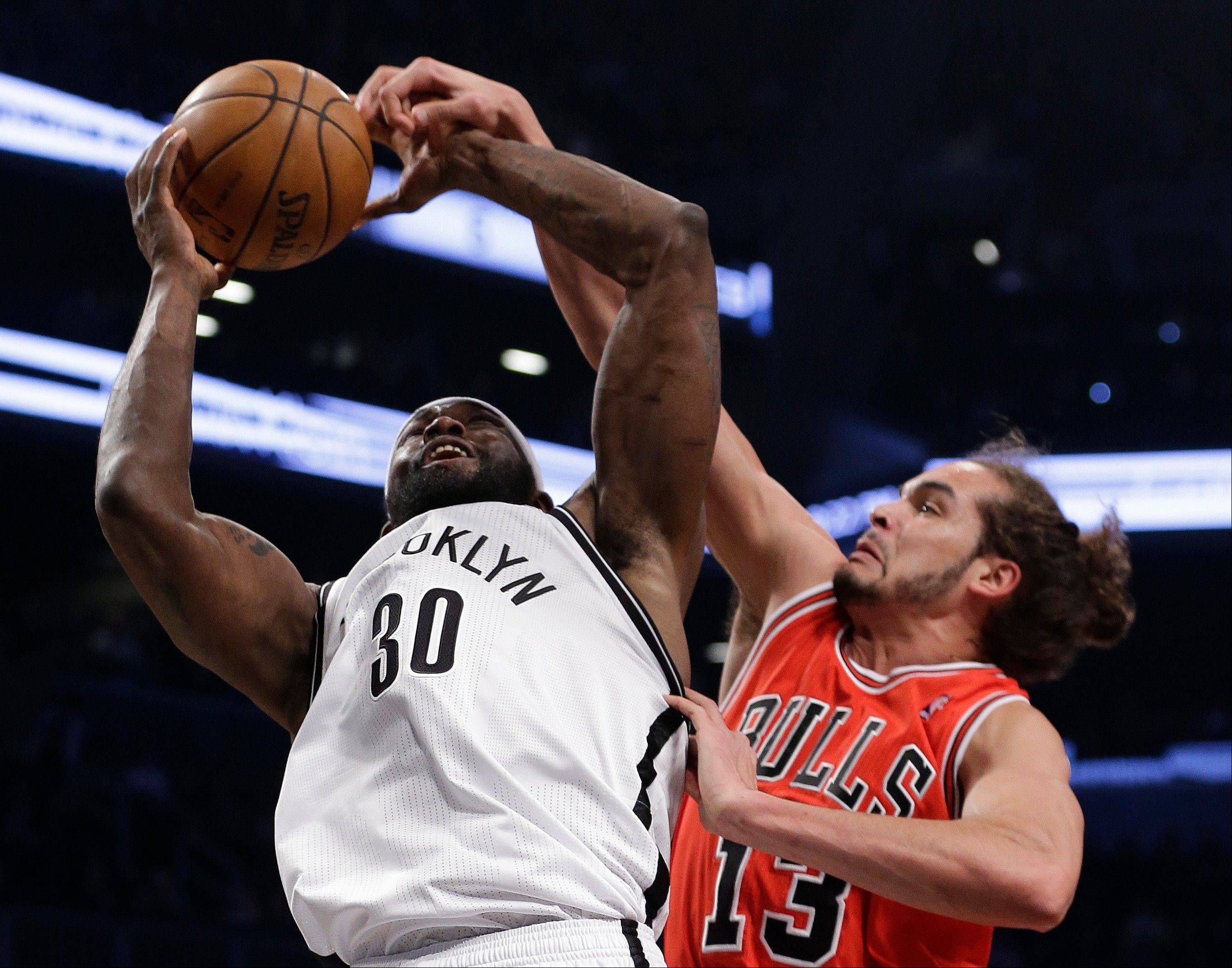 Bulls center Joakim Noah tries to block Brooklyn Nets forward Reggie Evans in the first half of Game 2 on Monday night.