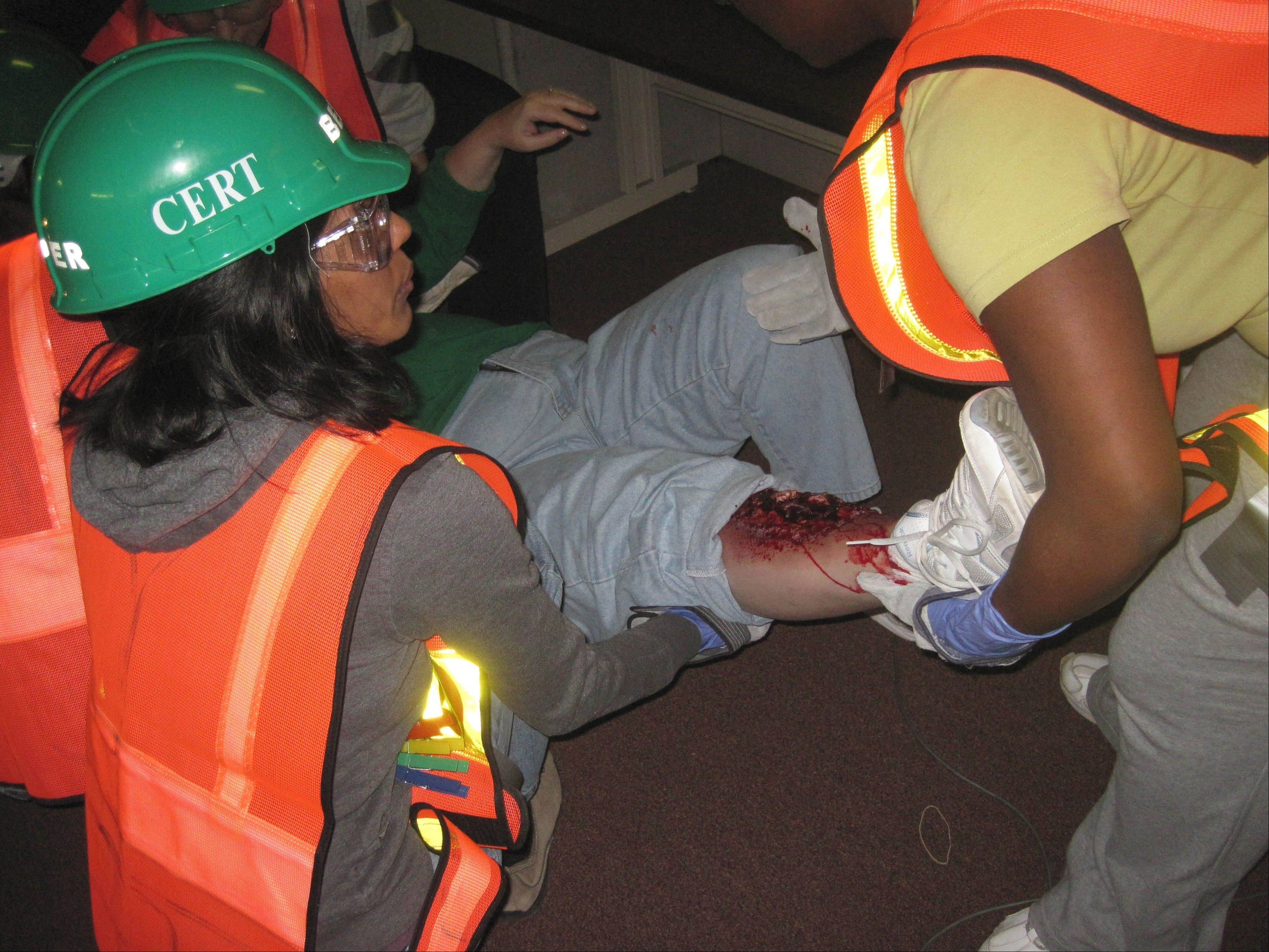 Nehal Patel and Abrial Jackson attend to a wound during a field training exercise held April 6 by the Palatine Emergency Management Agency.