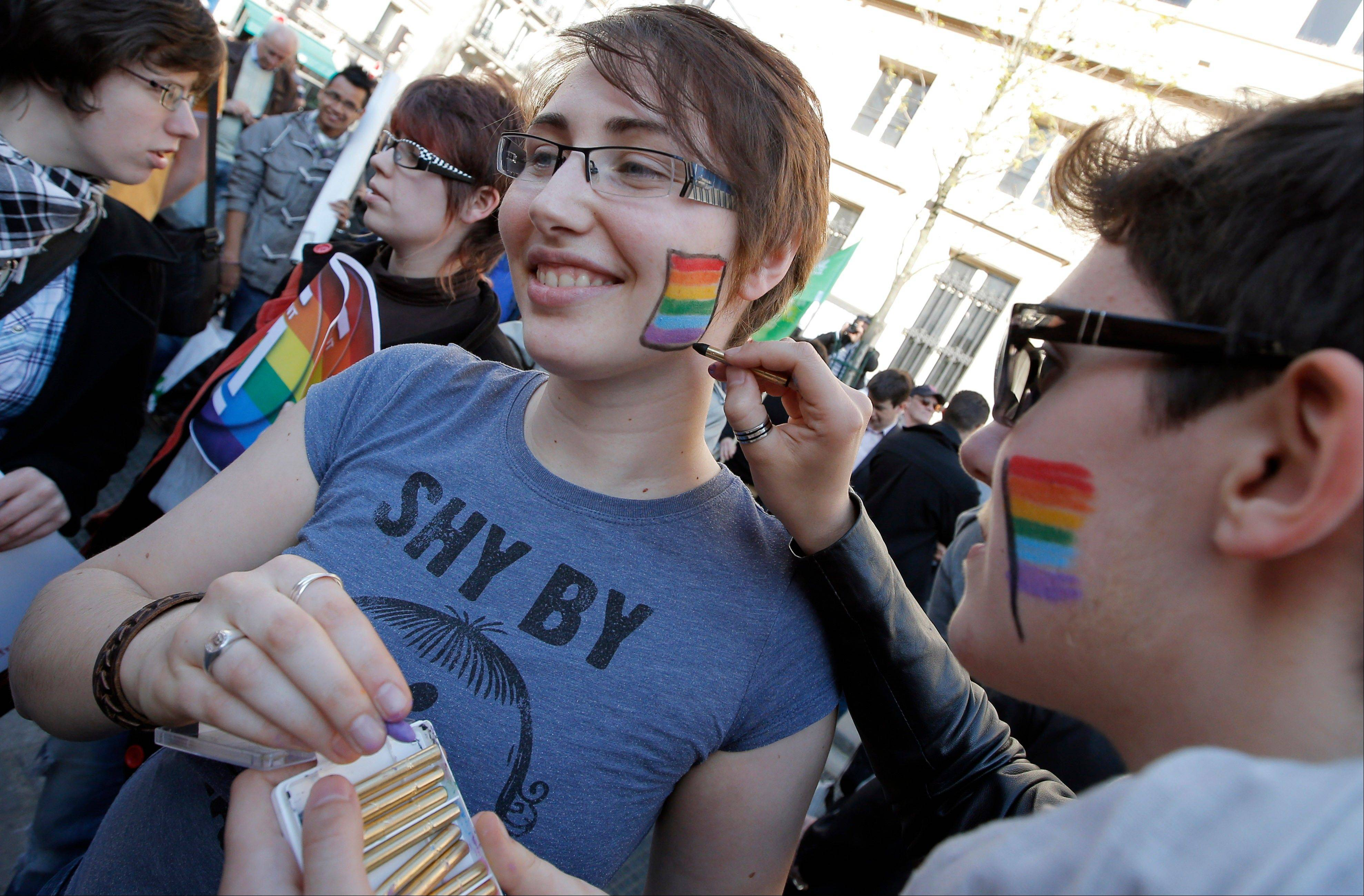 Pro gay marriage activists paint rainbow colors on their cheeks Tuesday after French lawmakers legalized same-sex marriage.