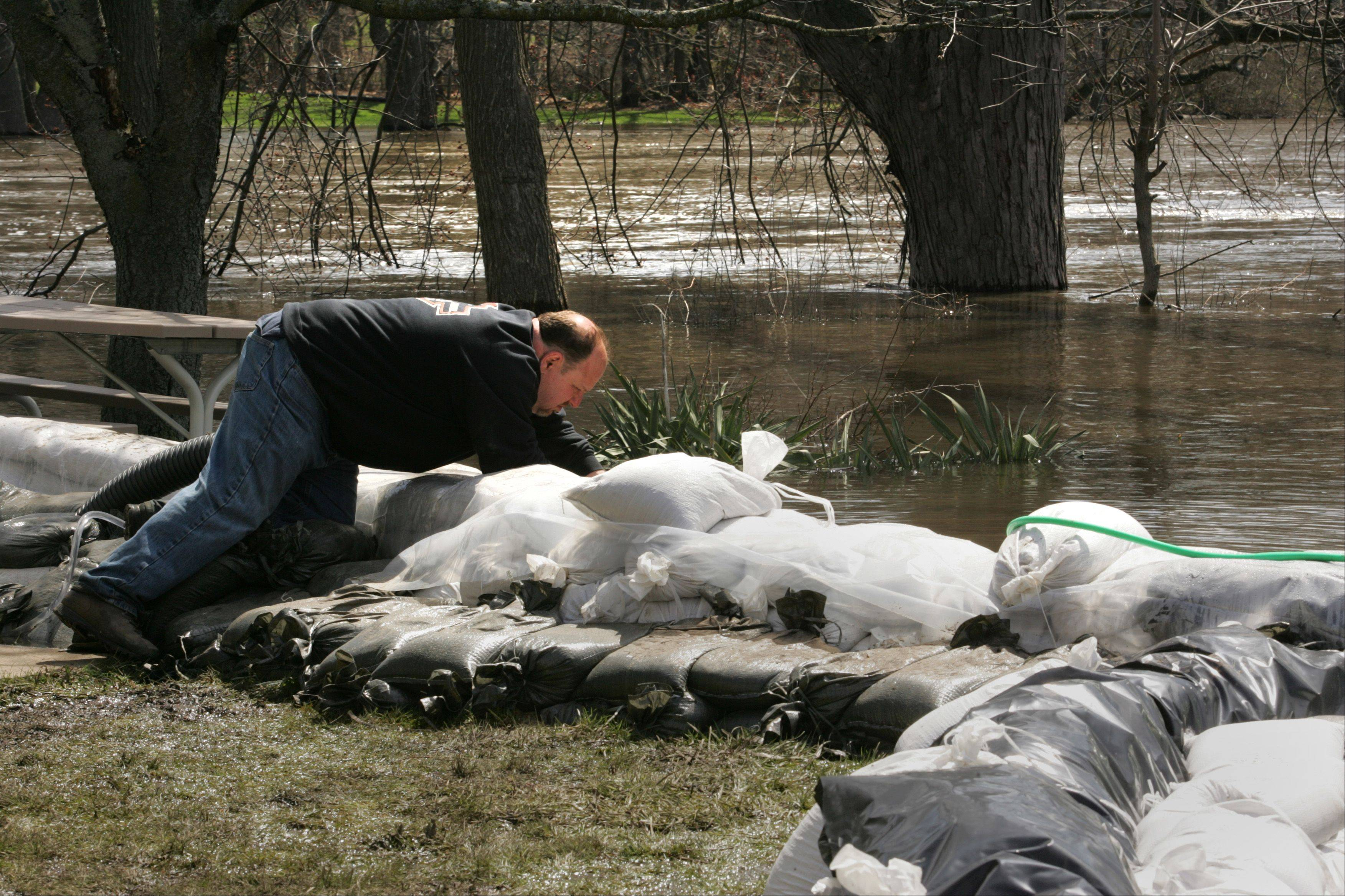 Algonquin resident Tony Angarola works to keep a sump pump hose in place behind his property along the Fox River Monday morning. Angarola rents the property to a tenant there, but has been working virtually around the clock to keep water from flooding the home.
