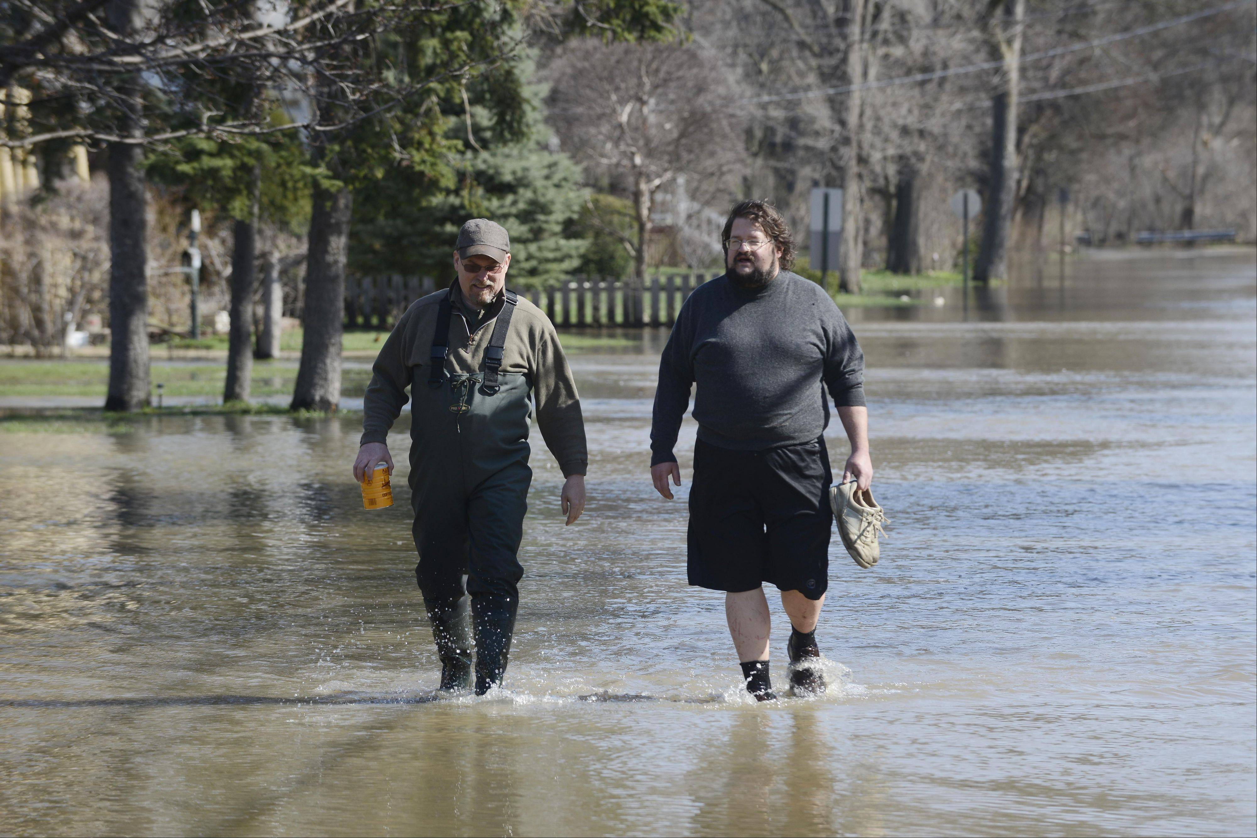 Kerry Chambers, left, and Andrij Karpenko walk along Hawthorne Lane as flooding from the Des Plaines River continues to recede from the Big Bend area in Des Plaines yesterday.