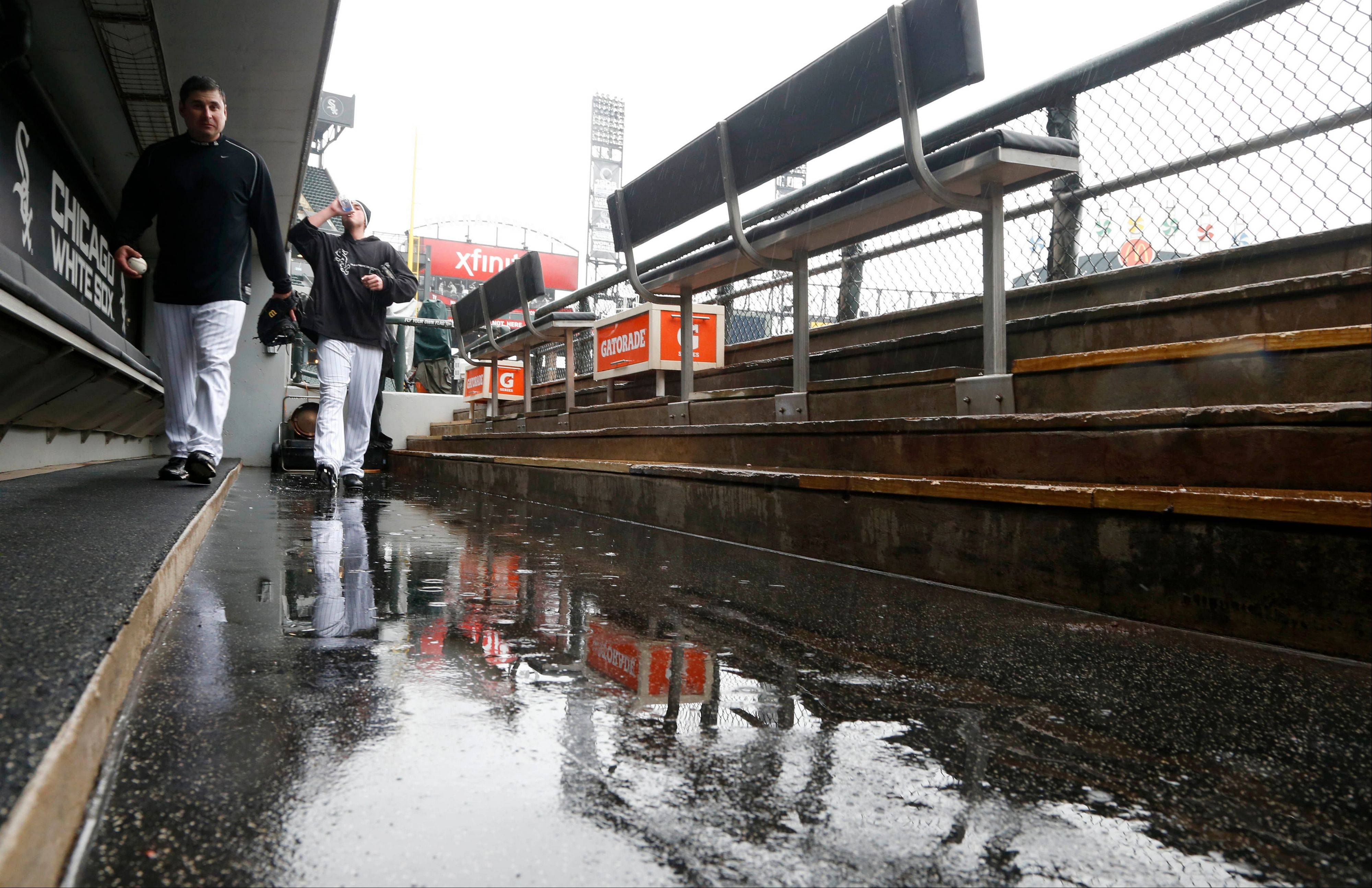 Chicago White Sox's bullpen coach Bobby Thigpen, left, and relief pitcher Addison Reed walk in and around the standing water in the dugout before a postponed baseball game that was called due to rain between the White Sox and the Cleveland Indians Tuesday, April 23, 2013, in Chicago. (AP Photo/Charles Rex Arbogast)