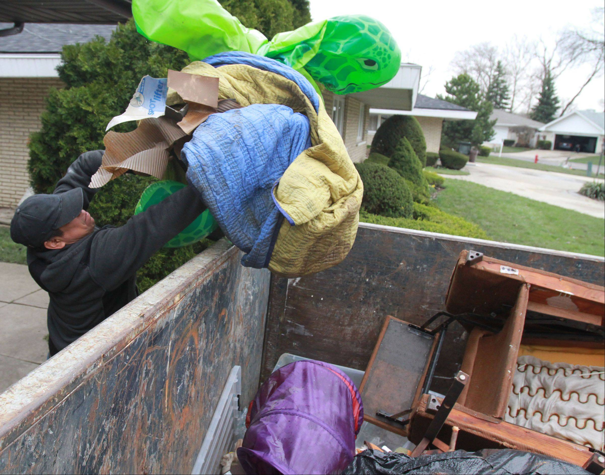 Danny Mateos, with Arthur J. Rogers and Company, throws toys into a dumpster at Kathi And Russell Fantetti's home on Berry Lane in Des Plaines on Tuesday, April 23. Kathi said they lost everything in the basement including furniture.