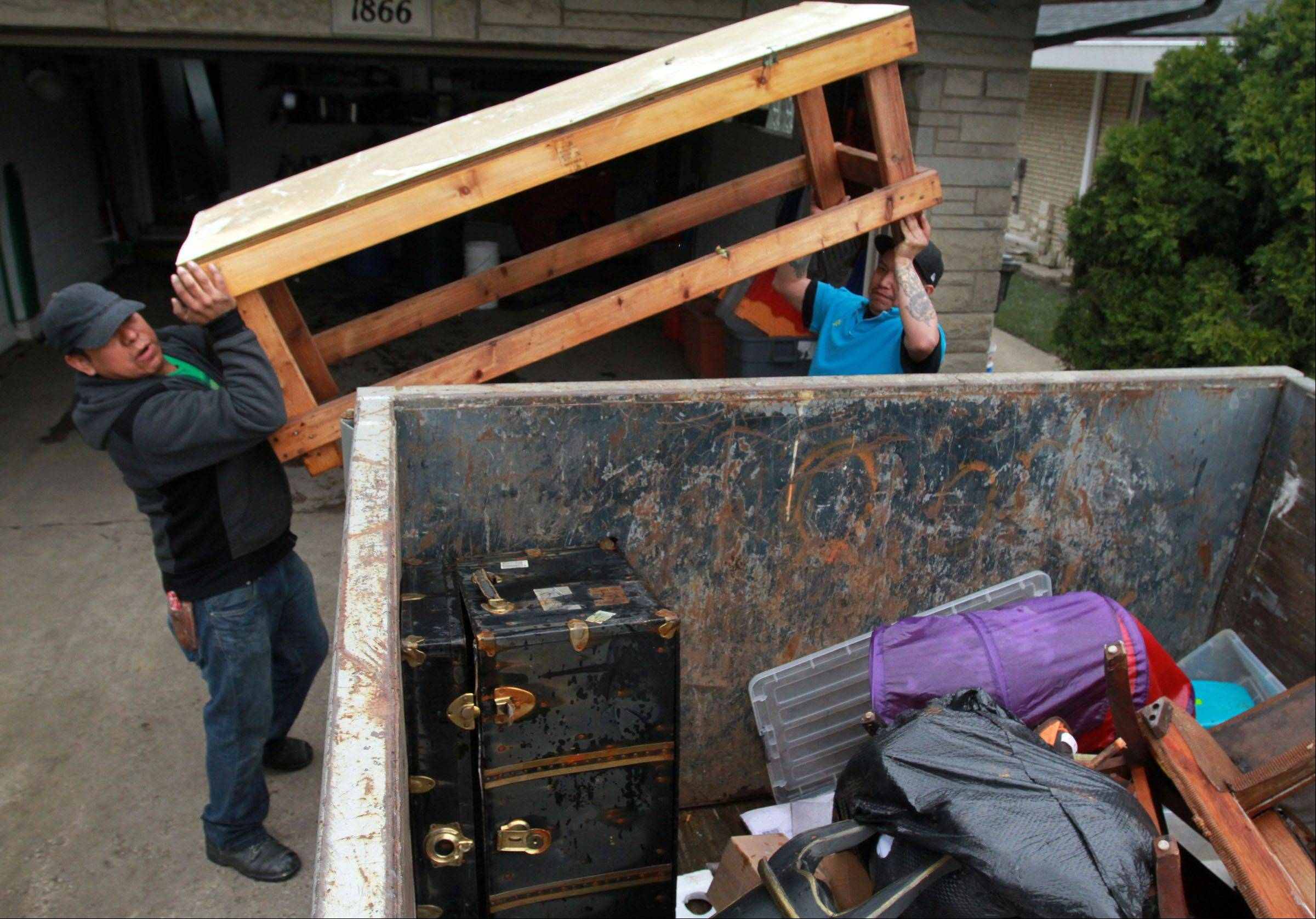 Danny Mateos, right, and Paco Matoes with Arthur J. Rogers and Company throw furniture in a dumpster from Kathi And Russell Fantetti's home on Berry Lane in Des Plaines on Tuesday, April 23. Kathi said they lost everything in the basement including furniture.