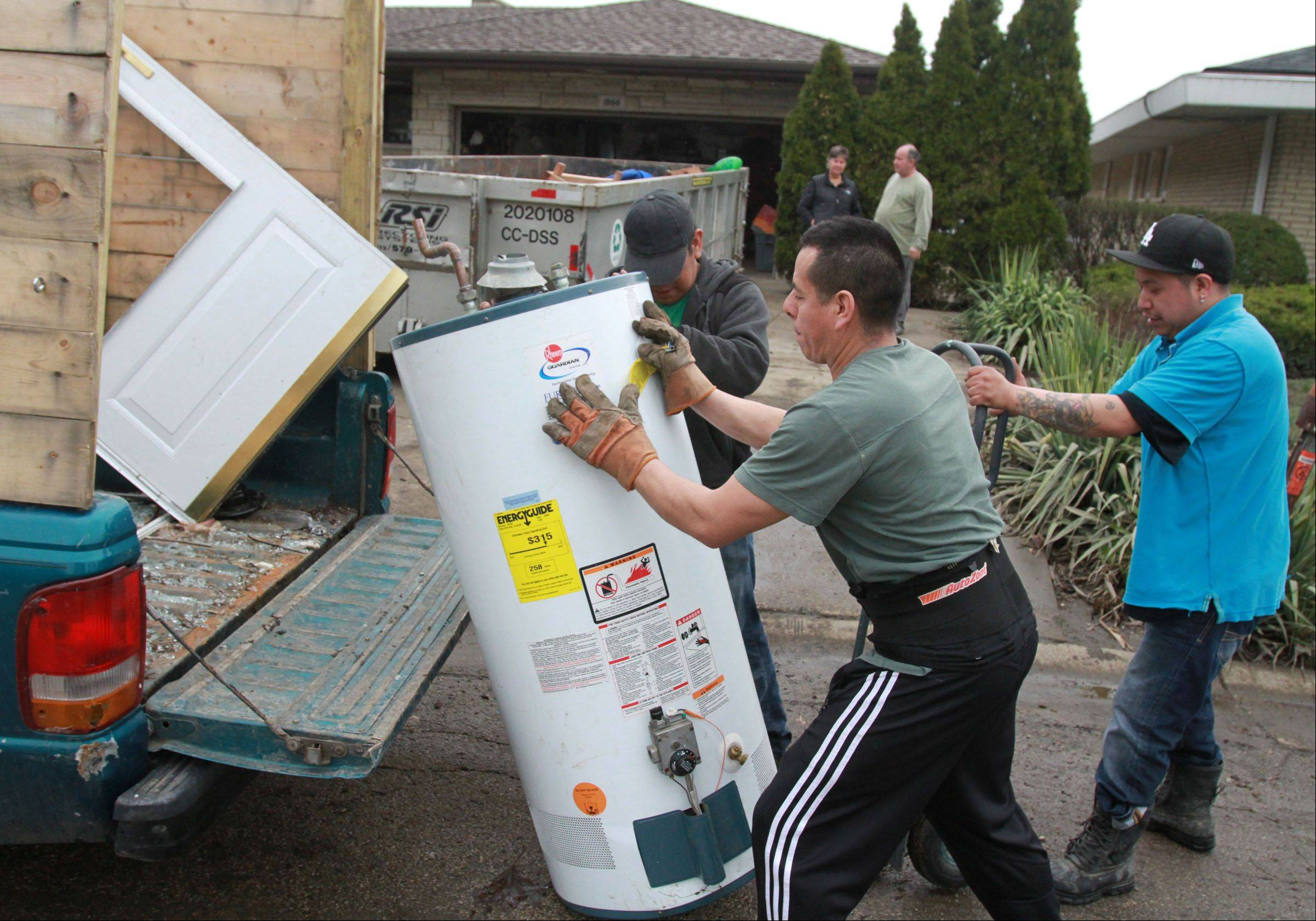 Danny Mateos, left, Paco Matoes, and Alex Ramirez, foreground, with Arthur J. Rogers and Company, remove a hot water heater from Kathi and Russell Fantetti's home on Berry Lane in Des Plaines on Tuesday.