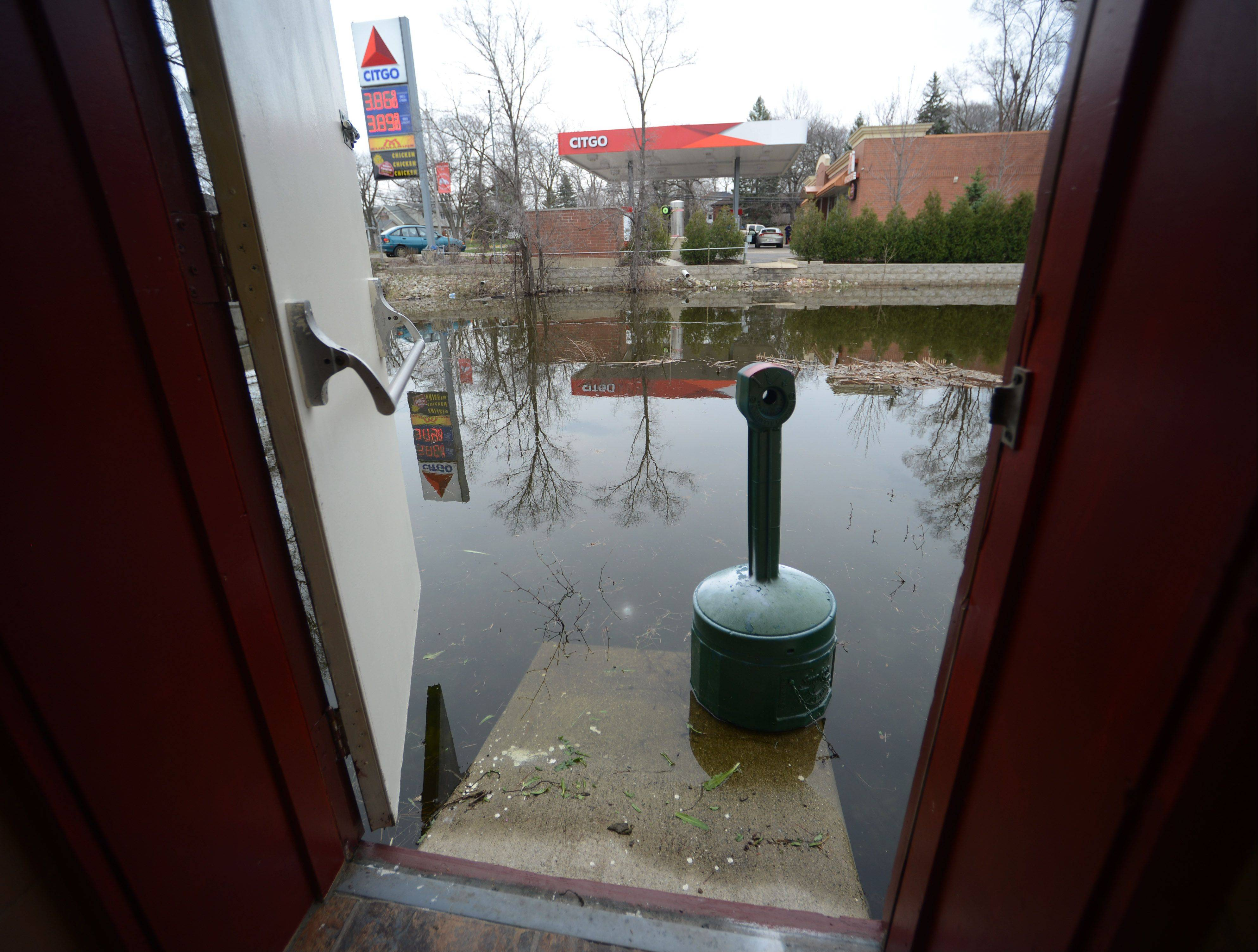 The floodwaters begin to recede at a side door of Channel Inn Fine Wine & Spirits on Grand Ave. in Fox Lake Tuesday morning.