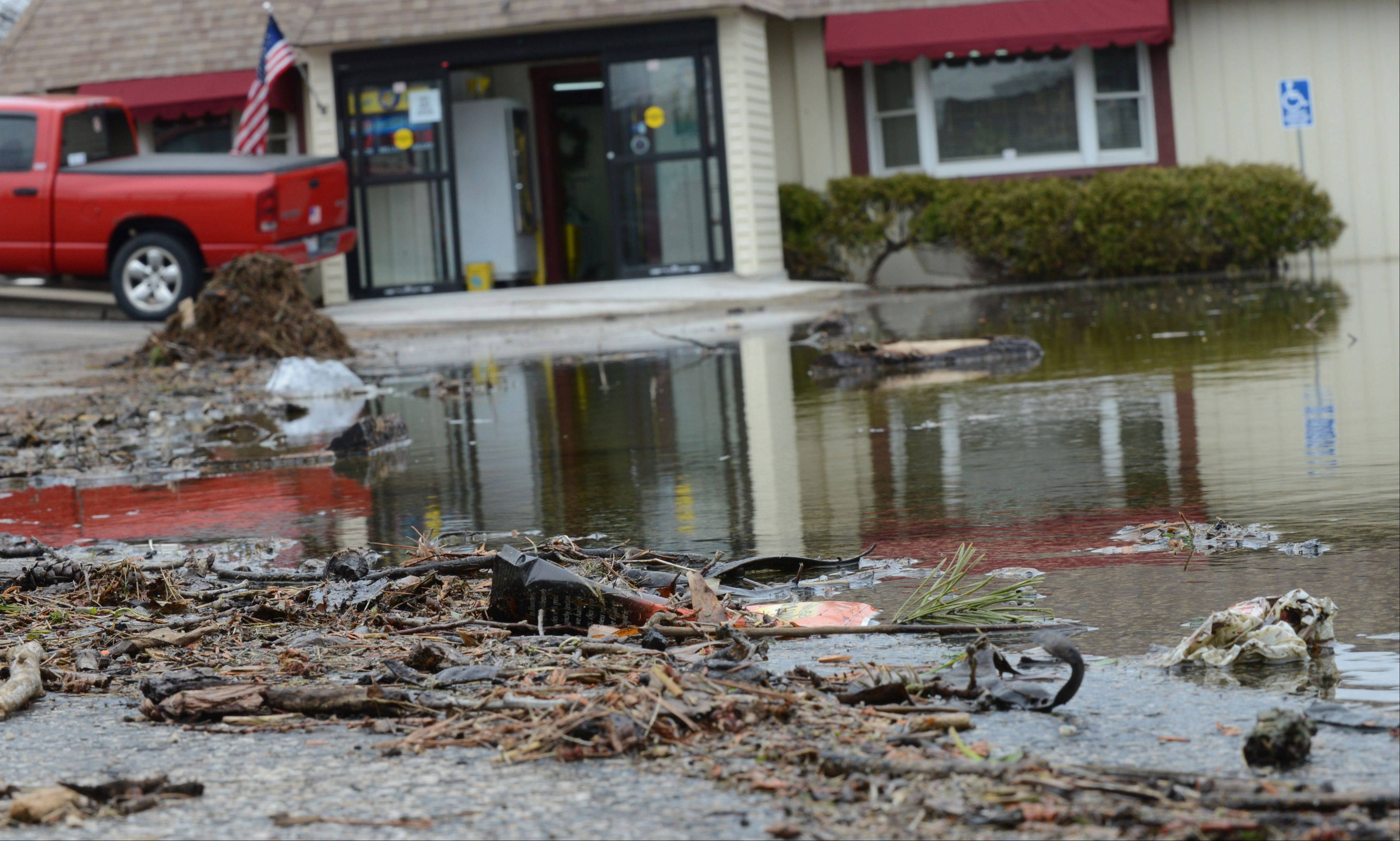 Debris left behind in the flooded parking lot of Channel Inn Fine Wine & Spirits on Grand Ave. in Fox Lake Tuesday morning.