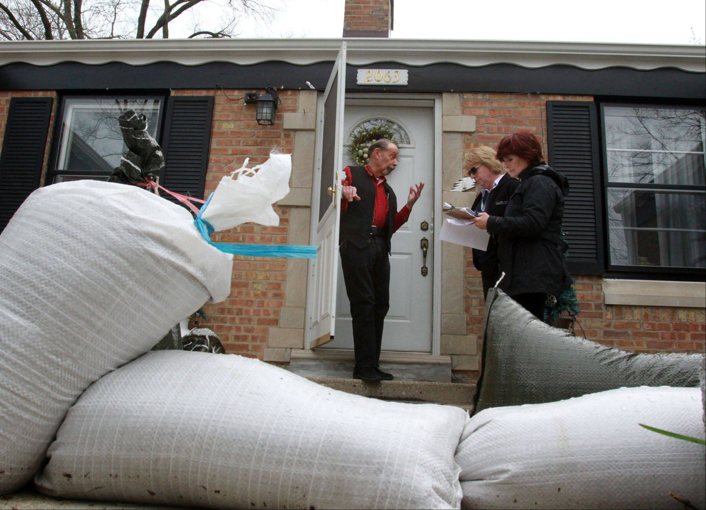 Des Plaines building inspectors Davorka Kirincic and Pam Lunsmann ask John Marton on Birch Street about flooding in his home and yard in Des Plaines on Tuesday, April 23.