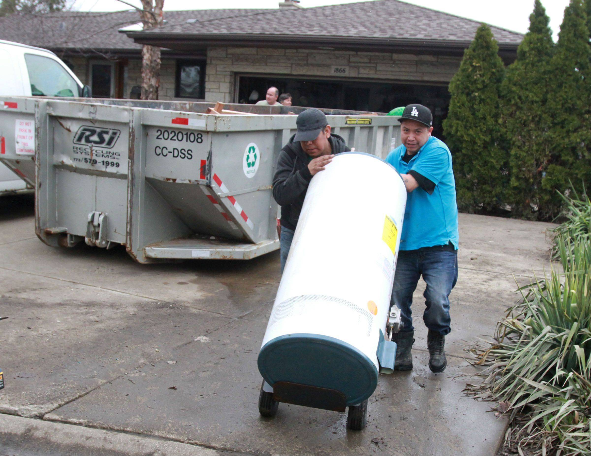 Danny Mateos and Paco Matoes with Arthur J. Rogers and Company, remove a hot water heater from Kathi and Russell Fantetti's Des Plaines home on Tuesday. Kathi said they lost everything in the basement including furniture.