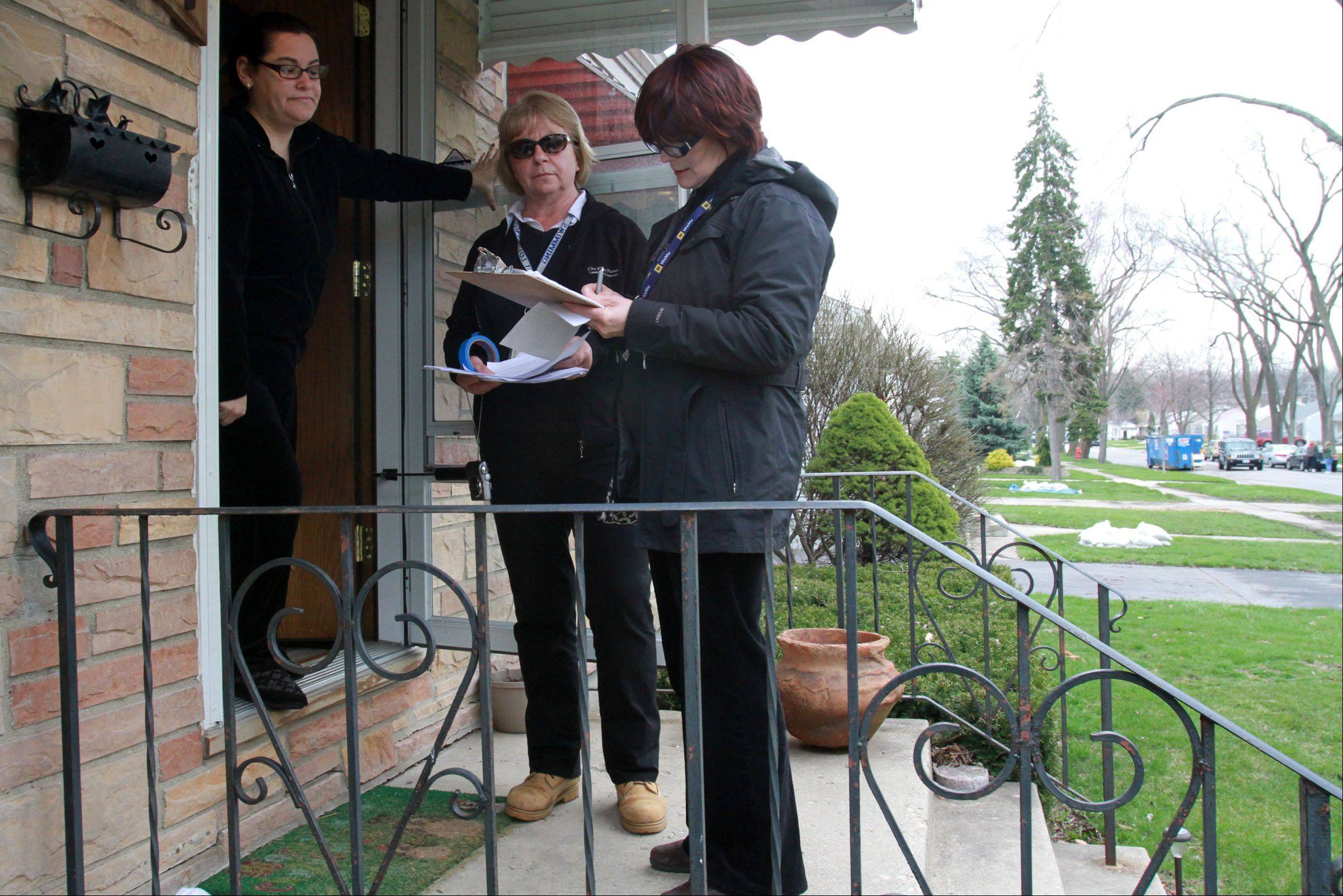 Des Plaines building inspectors Davorka Kirincic, right, and Pam Lunsmann ask Nicole Posen about flooding in her home and yard on Tuesday.