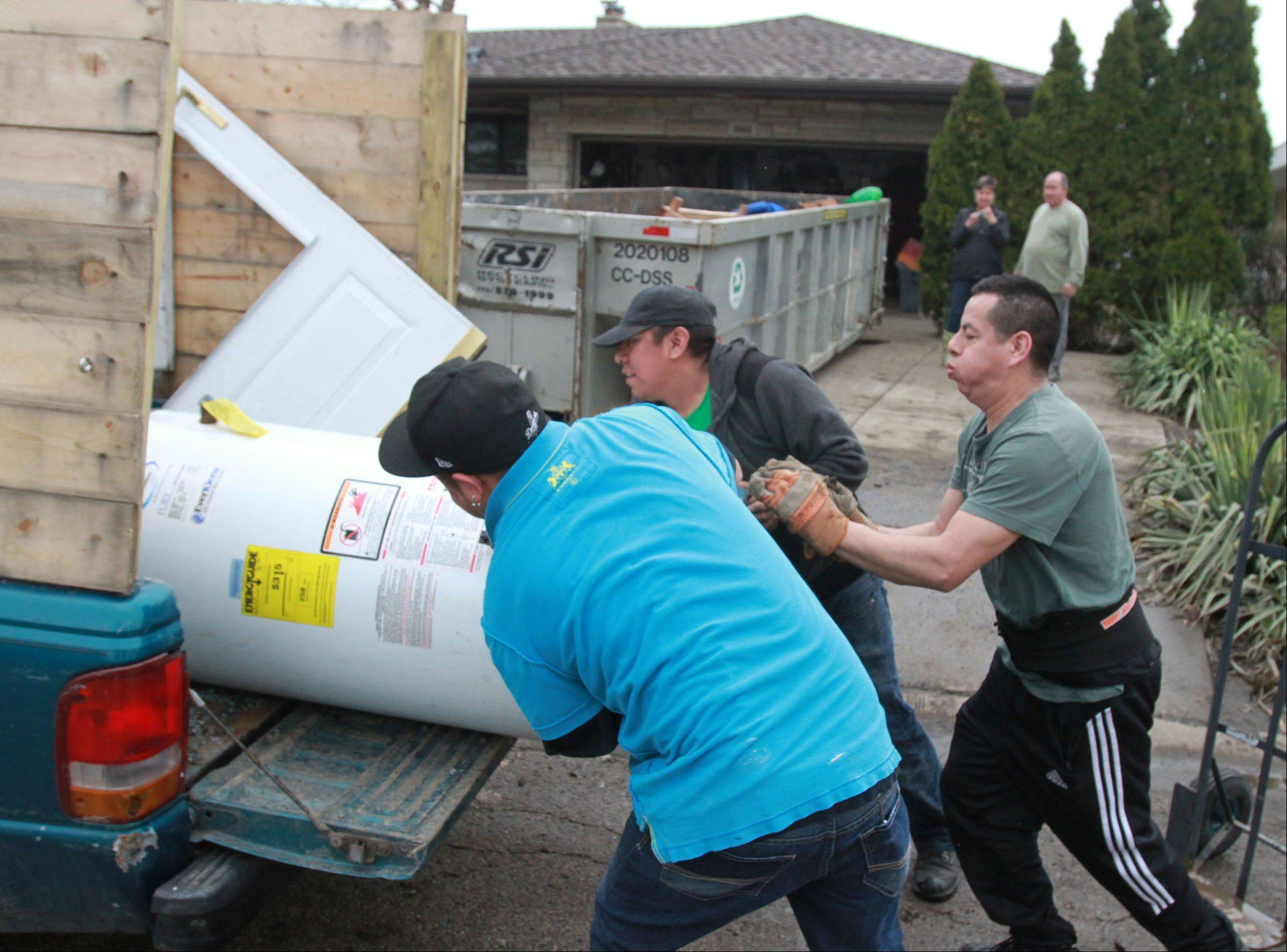 Danny Mateos, foreground, Paco Matoes, and Alex Ramirez, right, with Arthur J. Rogers and Company, remove a hot water heater from the home of Kathi and Russell Fantetti, in background, on Berry Lane in Des Plaines Tuesday. Kathi Fantetti said they lost everything in the basement, including furniture, because of flooding.