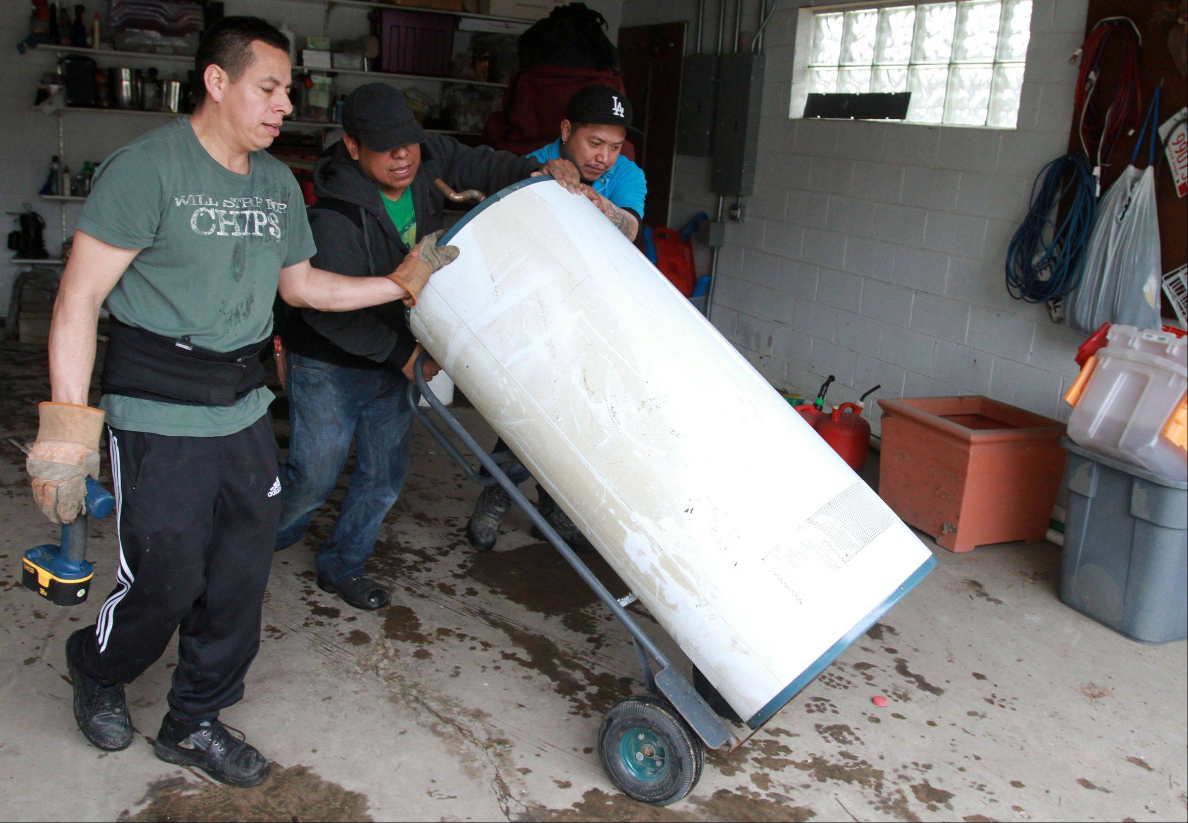 Danny Mateos, Paco Matoes, and Alex Ramirez, of Arthur J. Rogers and Company, remove a hot water heater from the home of Kathi and Russell Fantetti, in background, on Berry Lane in Des Plaines on Tuesday.