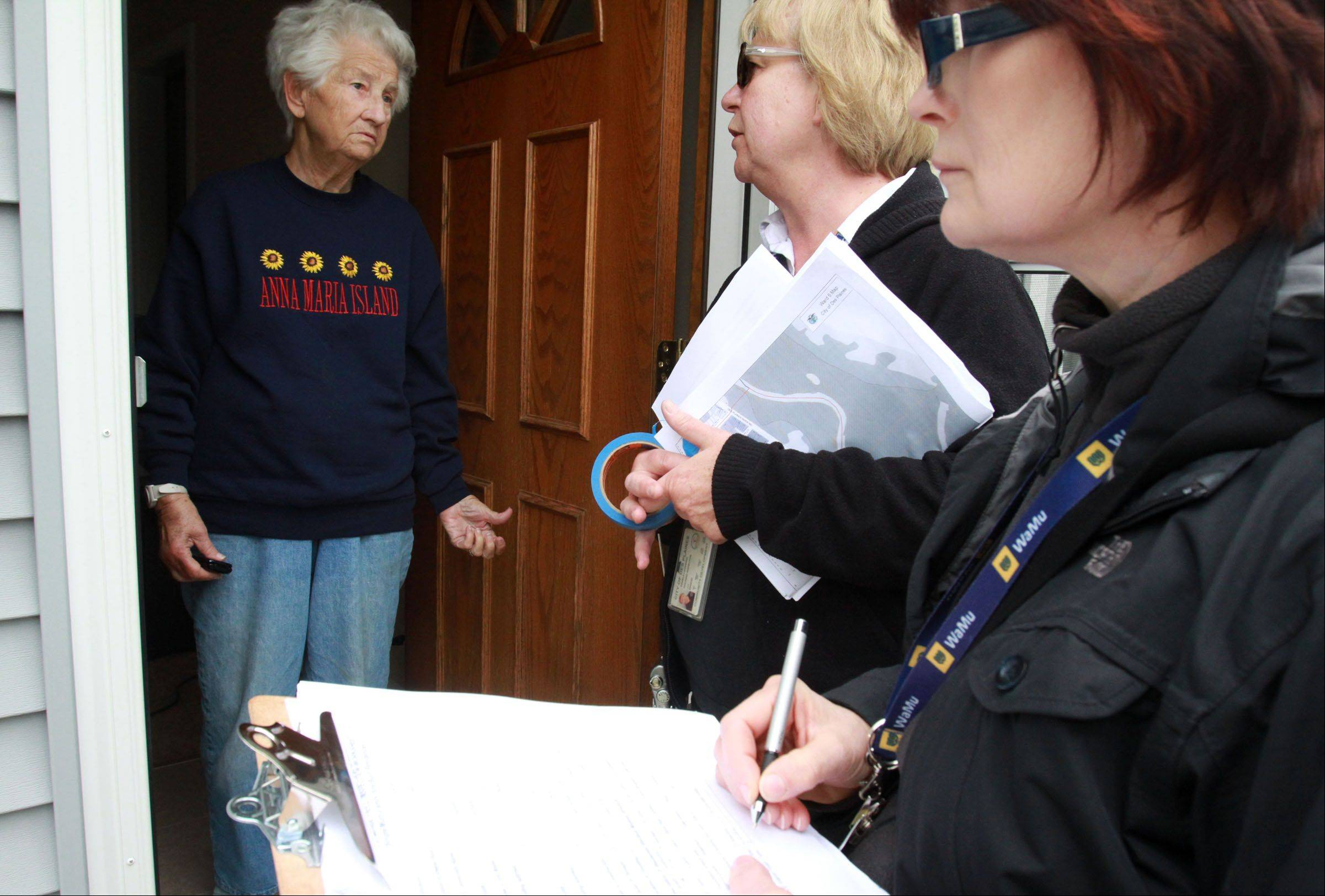 Des Plaines building inspectors Davorka Kirincic, right, and Pam Lunsmann ask Elizabeth Heyse, a resident of Fargo Avenue, about flooding in her home and yard Tuesday.