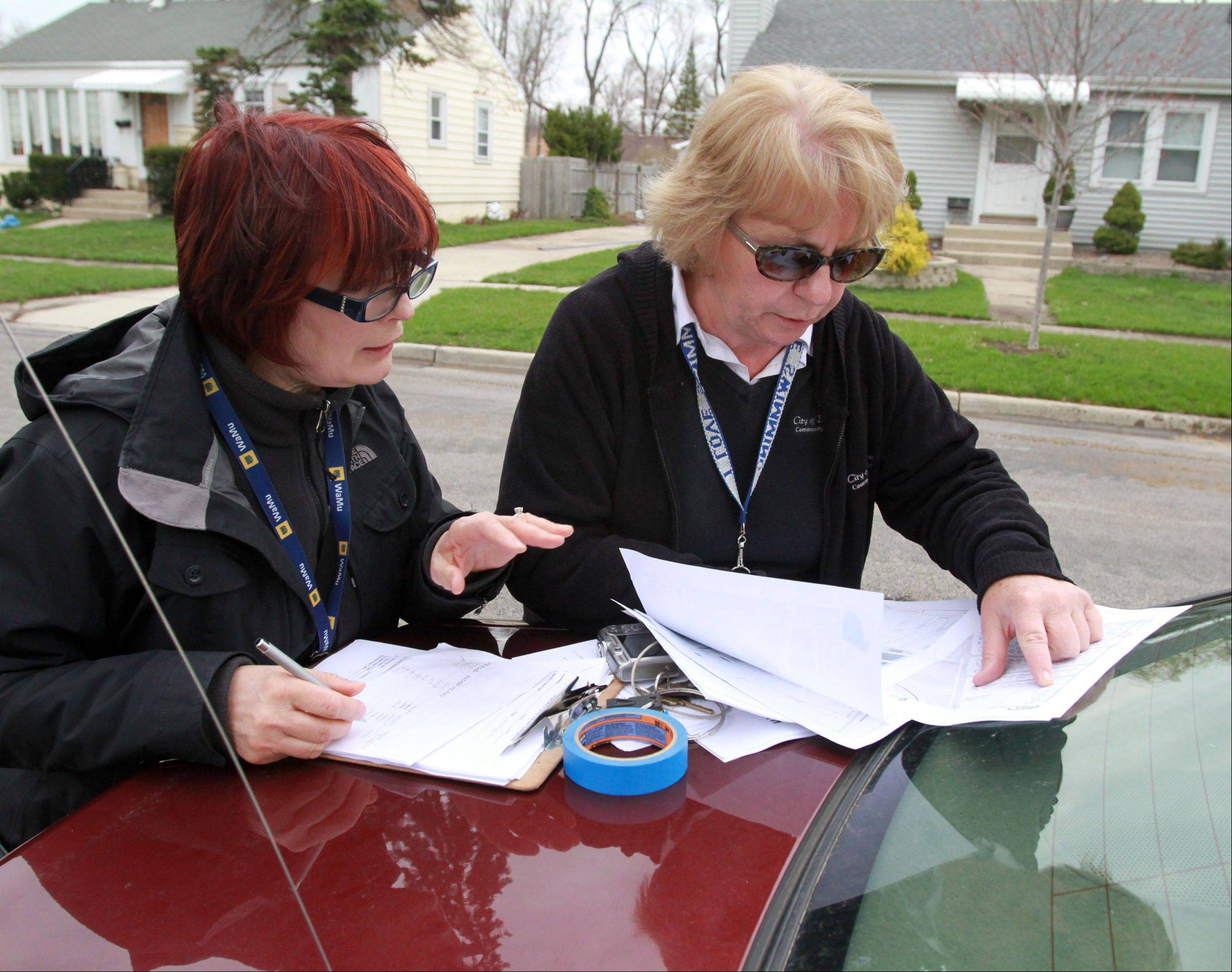 Des Plaines building inspectors Davorka Kirincic, left, and Pam Lunsmann check a map on Fargo Avenue before going door-to-door checking homes for flood damage in Des Plaines Tuesday.