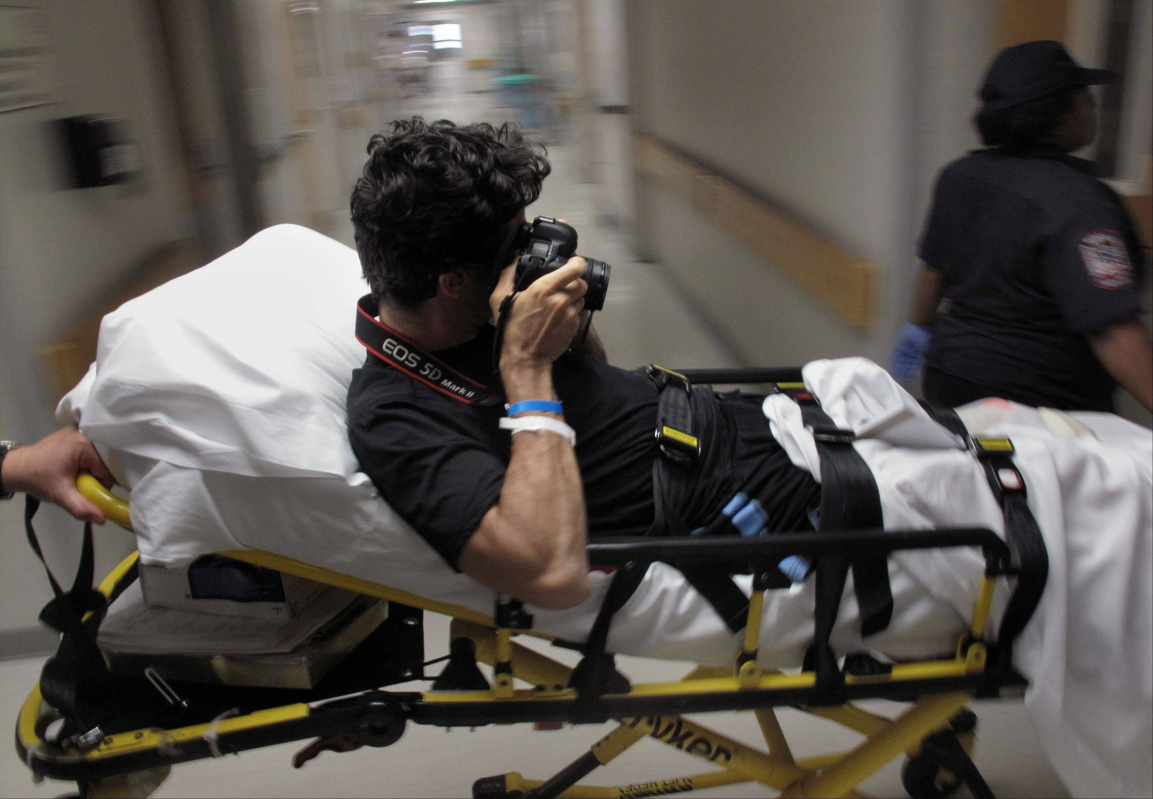 In this Aug. 25, 2009 picture, photographer Emilio Morenatti takes pictures as he is carried on a stretcher at University of Maryland Medical Center's R. Adams Cowley Shock Trauma Center in Baltimore, Md. For those who lost a limb or more in the Boston Marathon, Monday, April 15, 2013, was the day their world changed forever. Emilio's world changed on Tuesday, Aug. 11, 2009, in southern Afghanistan when the eight-wheel armored Stryker vehicle he was traveling in with U.S. soldiers hit a roadside bomb and flipped over, knocking him unconscious. Morenatti lost his leg in the bomb blast.
