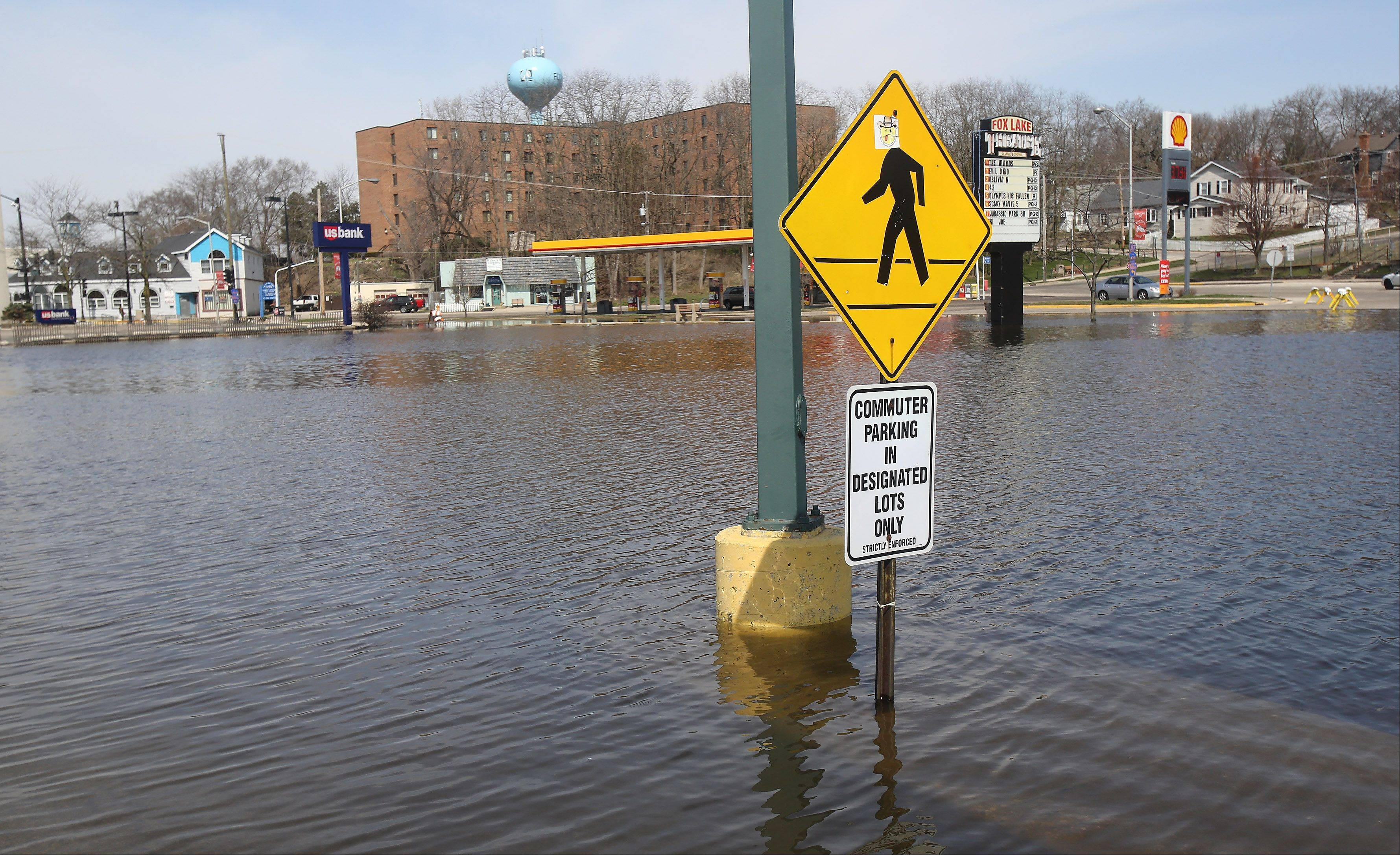 A shopping center parking lot and Grand Avenue are underwater in downtown Fox Lake on Monday after flooding from the Chain O' Lakes. The lake waters have still not receded and area residents are concerned about the forecast of rain on Tuesday.