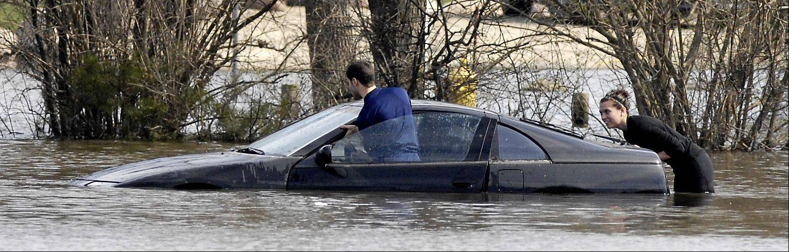 Victor and Ashley Atalla push the second of their two cars out of the floodwaters at Four Lakes subdivision in Lisle, Monday. The Atalla's were forced to park in the low lying area after the raised parking lot at the Towers at Four Lakes was full. The couple has only lived in their apartment for one year and were unaware of the potential for flooding in the parking lot.