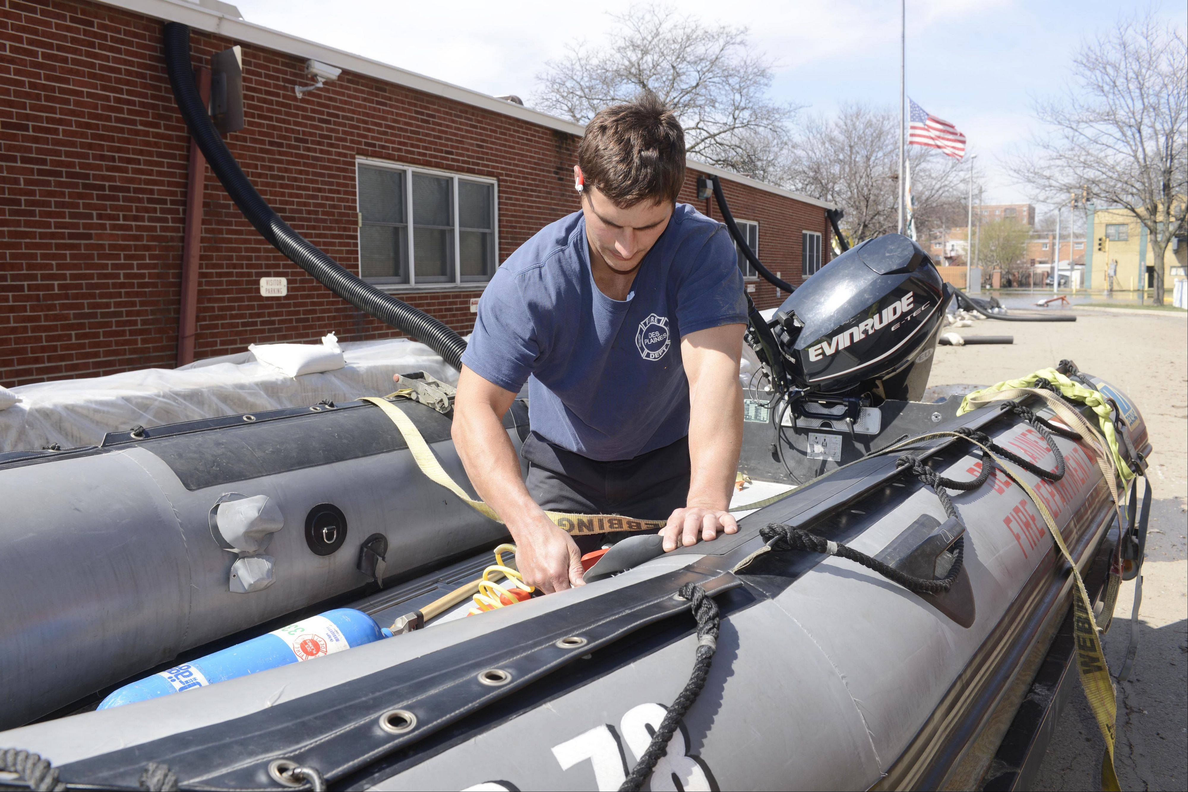 Firefighter/paramedic Ryan Petty gets the department's rescue boat ready for action outside the station at the intersection of Rive and Rand roads in Des Plaines Monday.
