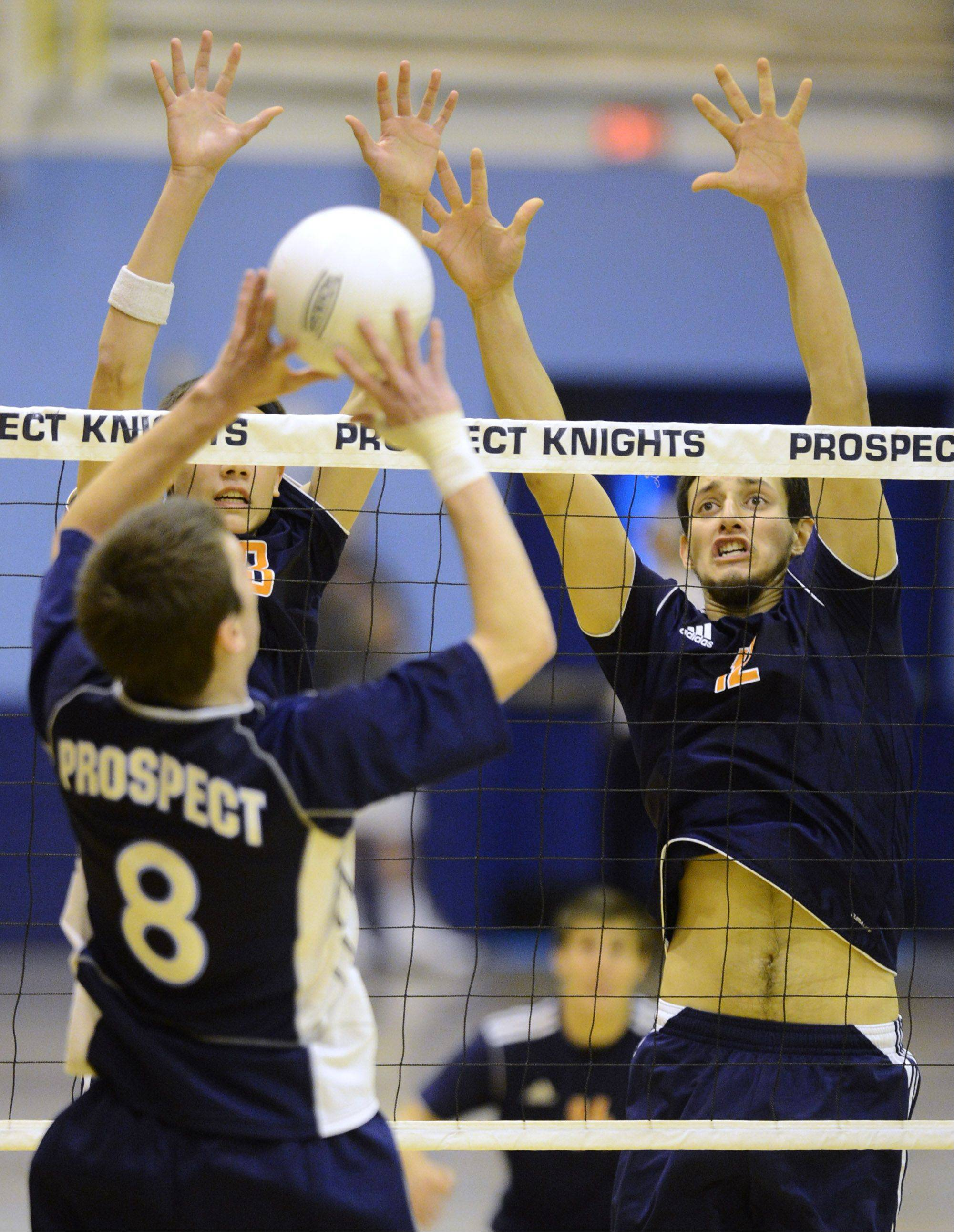 Prospect's Curtis Glennon taps the ball over the net in front of Buffalo Grove's Jose Aguirre, right, and Athan Cruz.