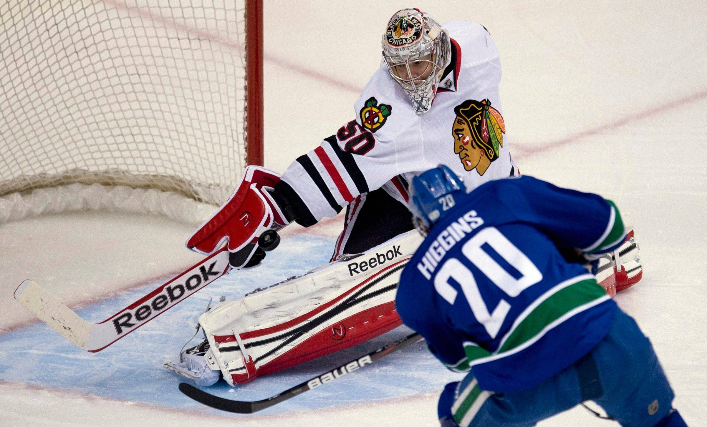 Vancouver Canucks left wing Chris Higgins (20) tries to get a shot past Chicago Blackhawks goaltender Corey Crawford during the first period of an NHL hockey game in Vancouver, B.C. on Monday, April 22, 2013.