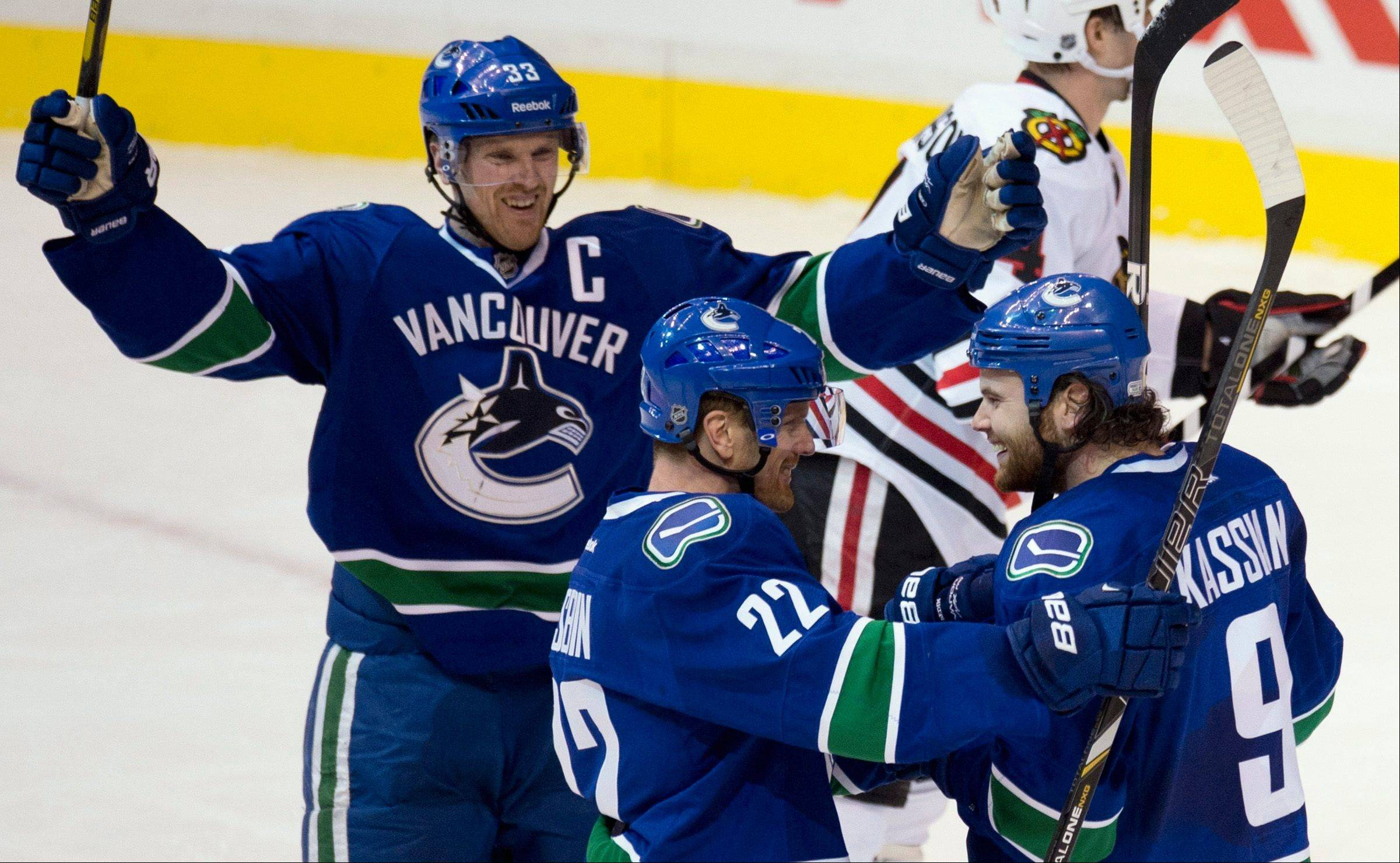 Vancouver Canucks right wing Zack Kassian (9) celebrates his goal against the Chicago Blackhawks with teammate Daniel Sedin (22) and Henrik Sedin (33) during the second period of an NHL hockey game in Vancouver, B.C. on Monday, April 22, 2013.
