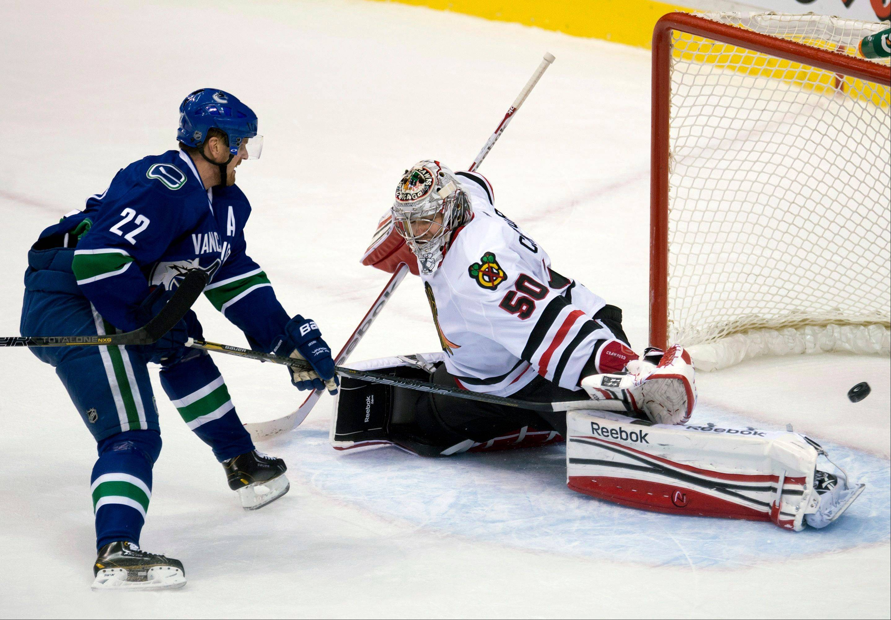 Vancouver Canucks left wing Daniel Sedin (22) scores against Chicago Blackhawks goalie Corey Crawford (50) during the second period of their NHL hockey game in Vancouver, British Columbia, Monday, April 22, 2013.