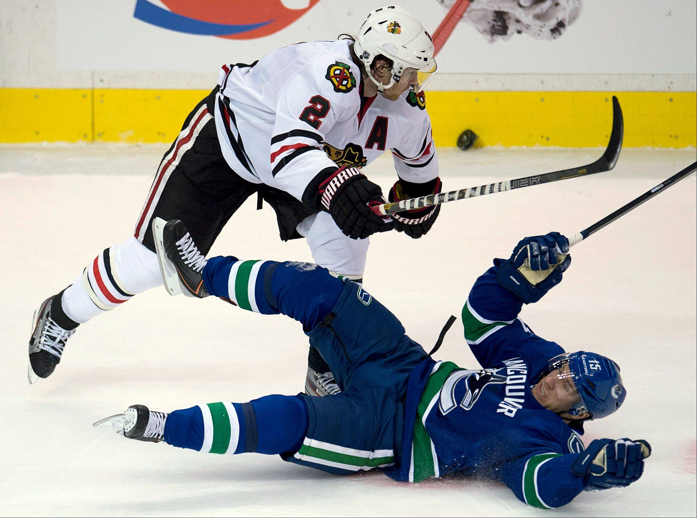 Vancouver Canucks center Derek Roy (15) fights for control of the puck with Chicago Blackhawks defenseman Duncan Keith (2) during the second period of their NHL hockey game in Vancouver, British Columbia, Monday, April 22, 2013.
