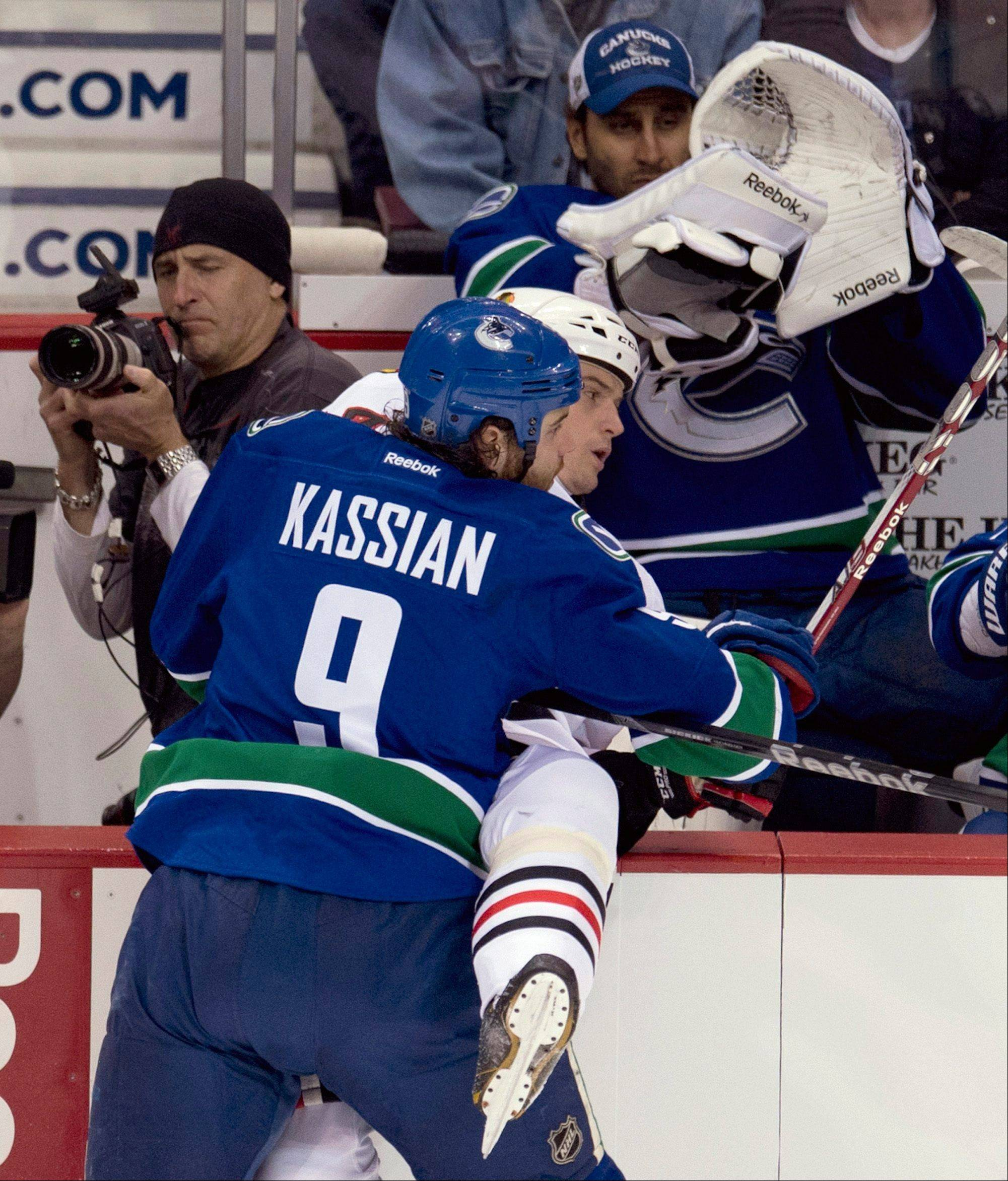 Vancouver Canucks right wing Zack Kassian (9) puts Chicago Blackhawks Sheldon Brookbank into the boards as Vancouver Canucks goalie Roberto Luongo (1) watches during the first period of an NHL hockey game in Vancouver, B.C. on Monday, April 22, 2013.