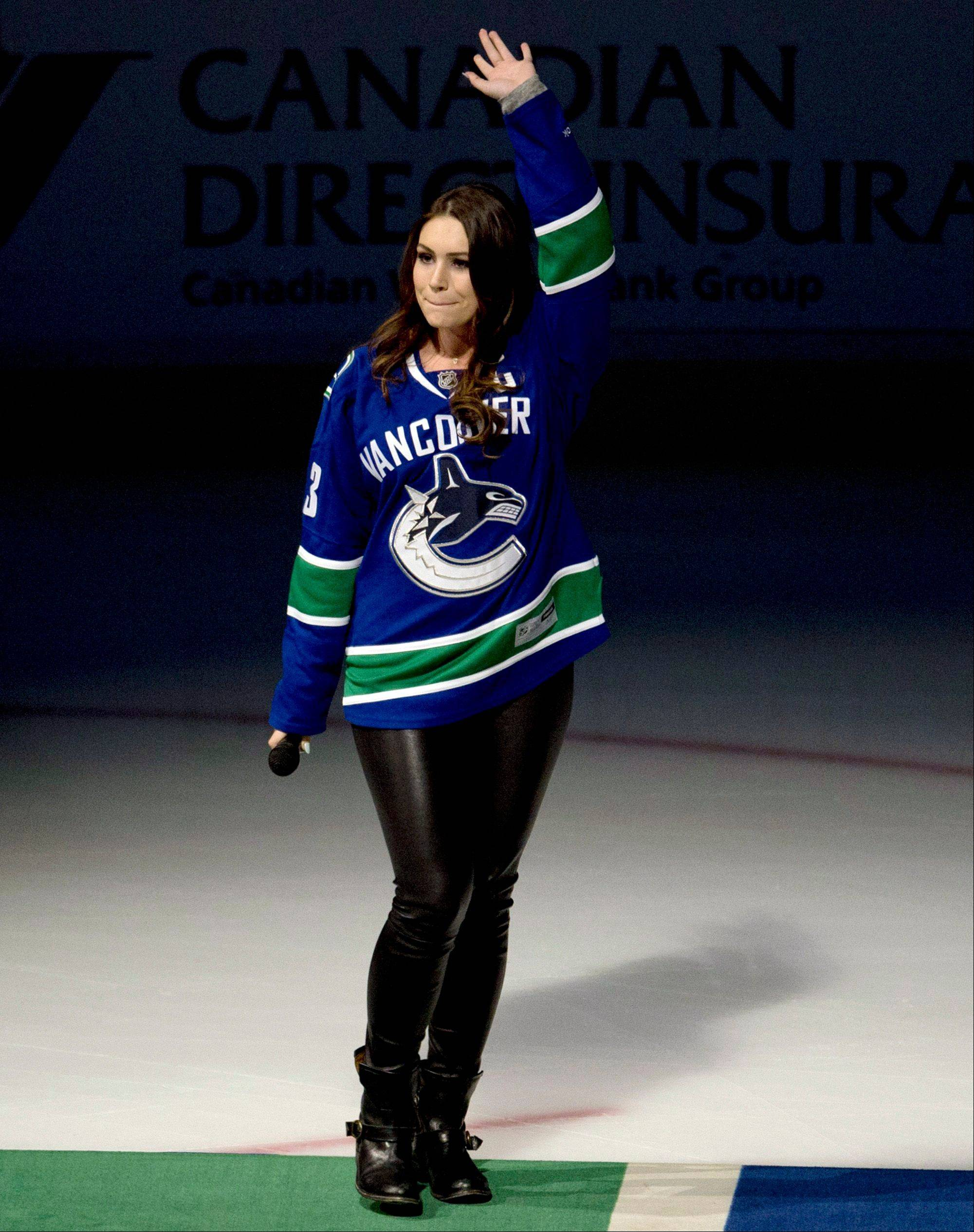 Sophie Tweed Simmons waves to the crowd after singing the national anthems prior to an NHL hockey game between the Vancouver Canucks and Chicago Blackhawks in Vancouver, B.C. on Monday, April 22, 2013.