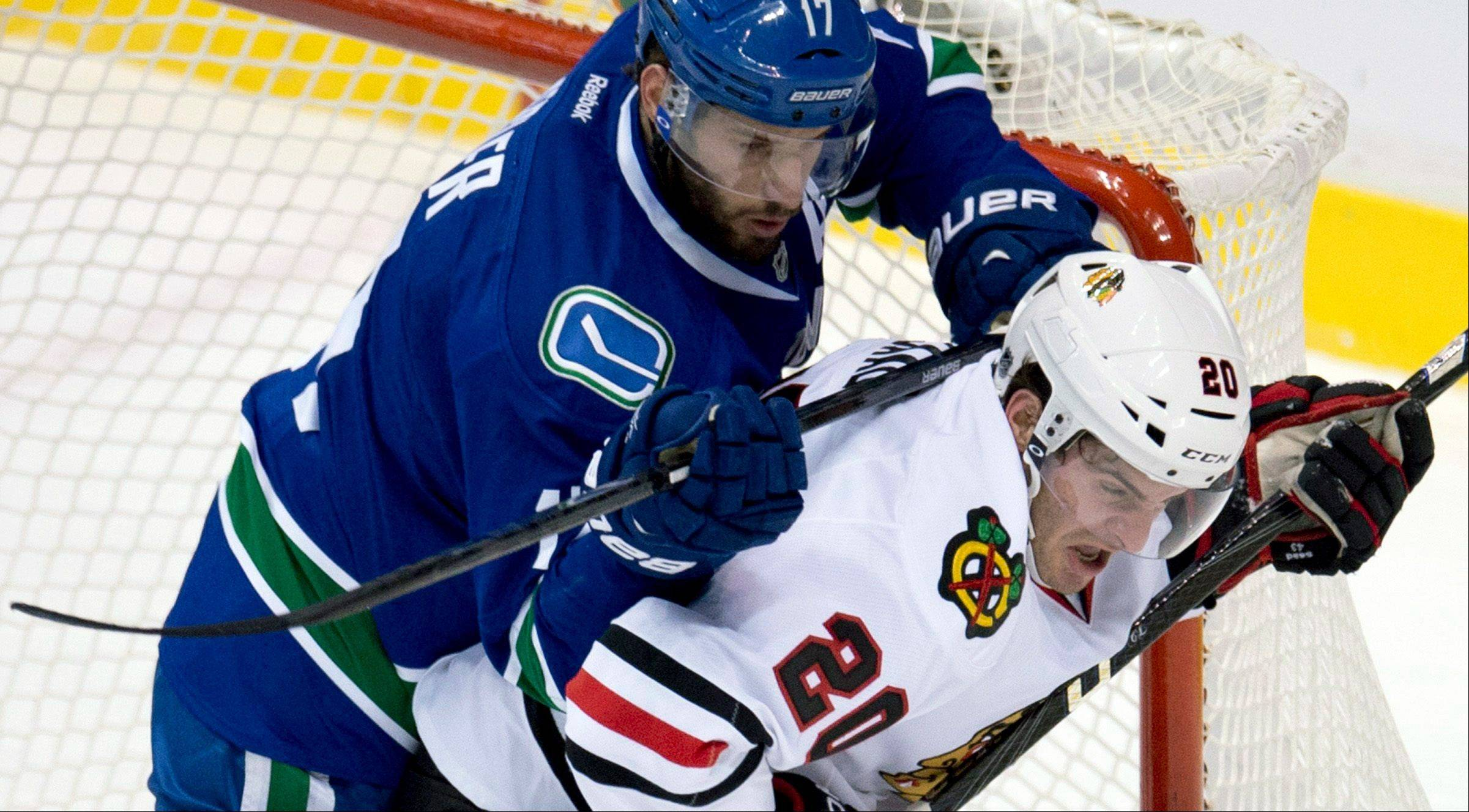 Vancouver Canucks center Ryan Kesler (17) tries to clear Chicago Blackhawks left wing Brandon Saad (20) from in front of the Canucks net during the first period of an NHL hockey game in Vancouver, B.C. on Monday, April 22, 2013.