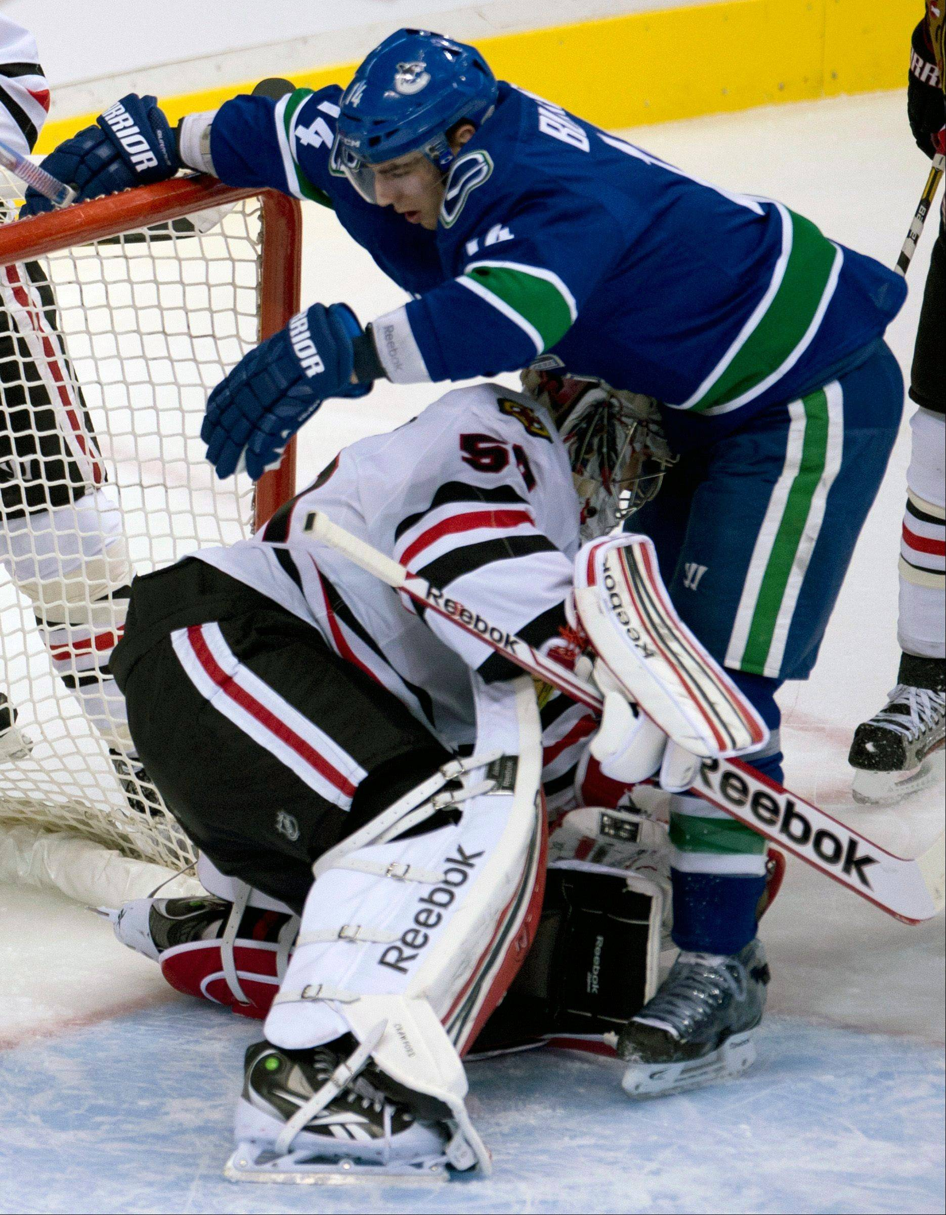 Vancouver Canucks center Alex Burrows (14) collides with Chicago Blackhawks goalie Corey Crawford (50) during the first period of an NHL hockey game in Vancouver, B.C. on Monday, April 22, 2013.
