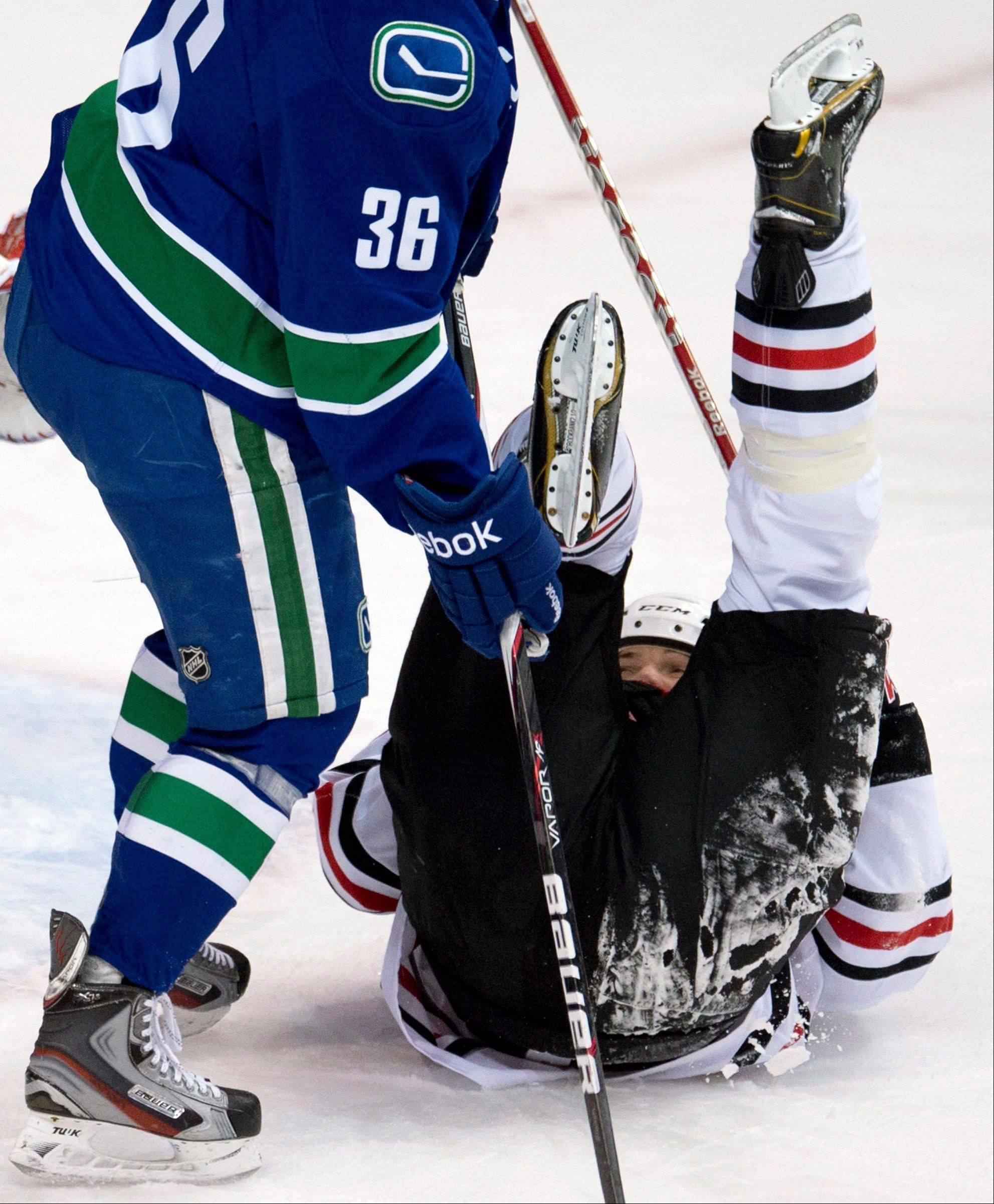 Vancouver Canucks right wing Jannik Hansen (36) skates near as Chicago Blackhawks defenseman Sheldon Brookbank (17) falls to the ice after being hit by the puck during the first period of their NHL hockey game in Vancouver, British Columbia, Monday, April 22, 2013.