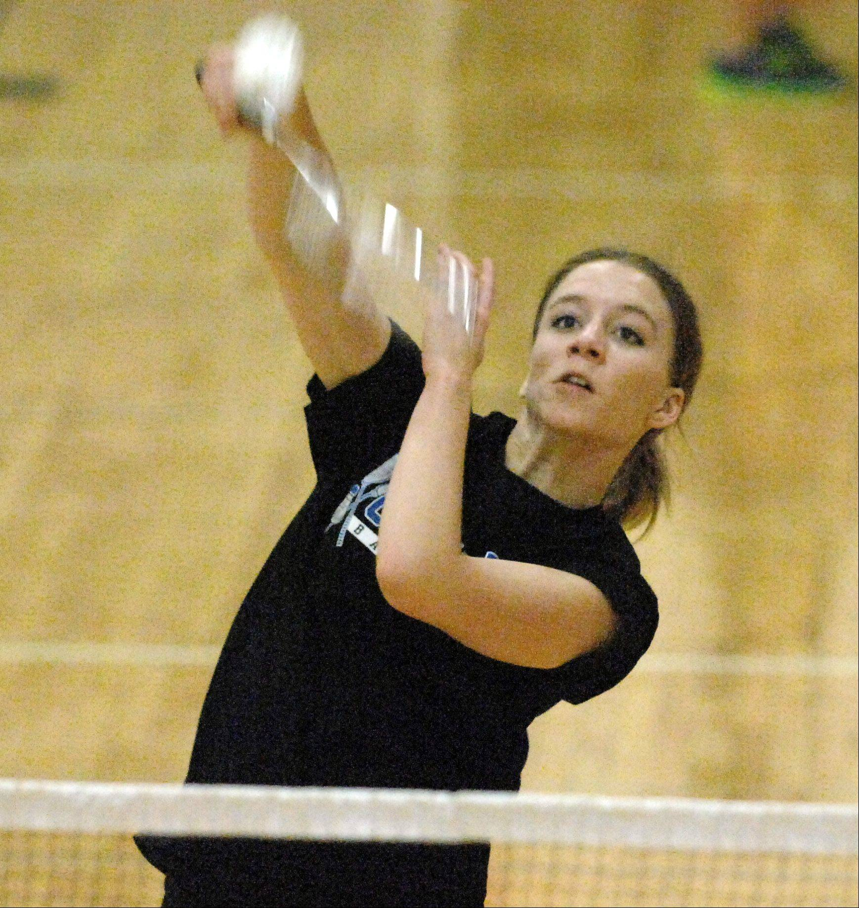 Geneva's Ann Green hits an overhead shot during her badminton match against St. Charles East on Thursday.