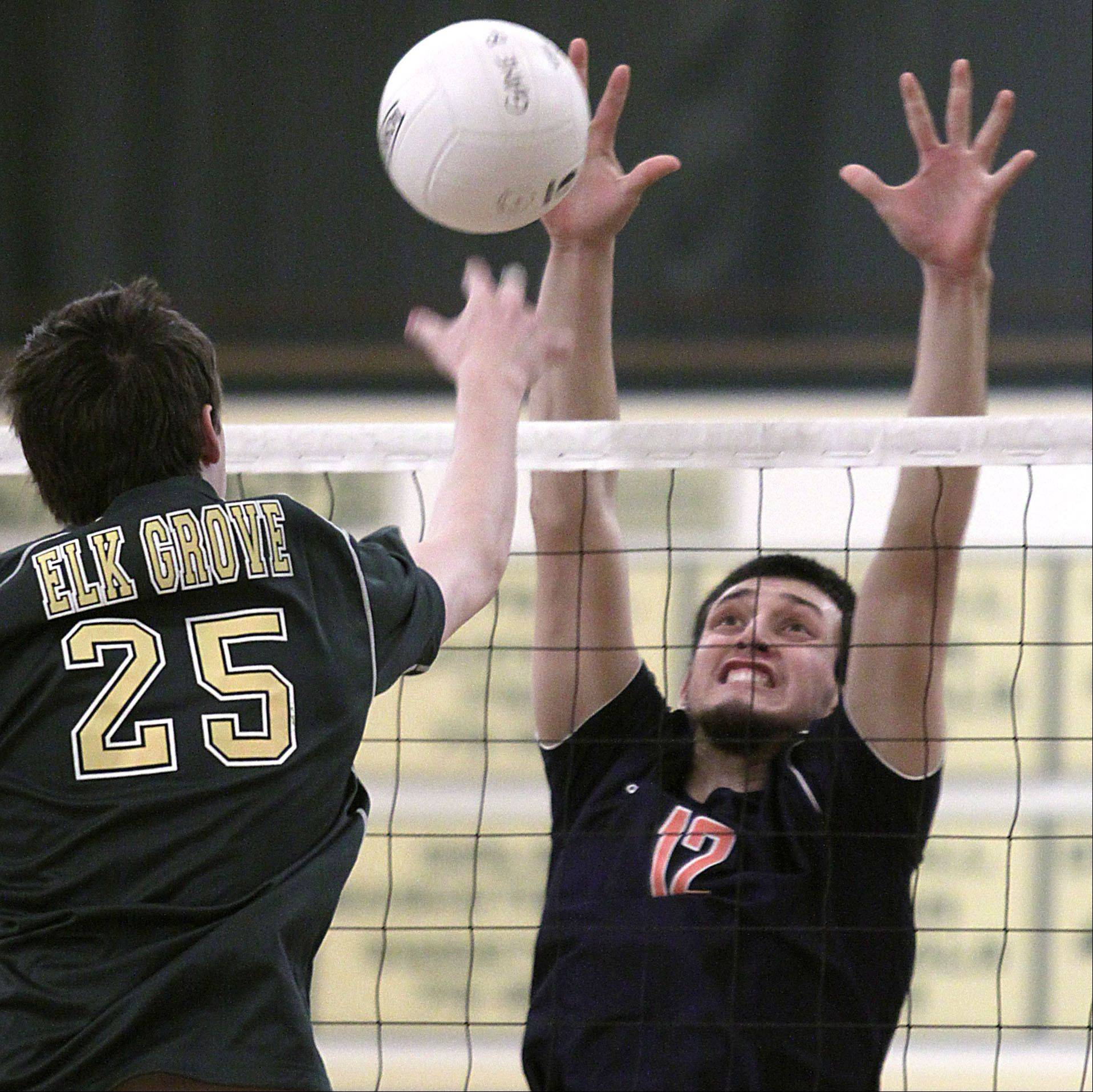 Elk Grove's Sam Jasutis, left, hits the ball against Buffalo Grove's Jose Aguirre during Tuesday's volleyball game against Elk Grove.