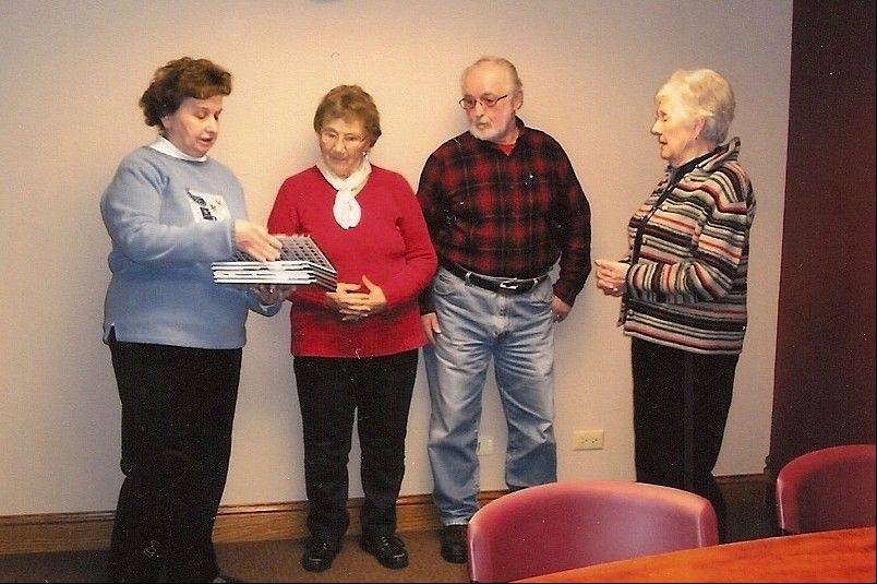 Hampshire-Henpeck HCE members Geri Rizik and Doris Klock present books to Patrick and Marie Herrmann in honor of the late Pearl Herrmann, a longtime member of HCE. The books will be donated to St. Charles Borromeo Catholic School library.