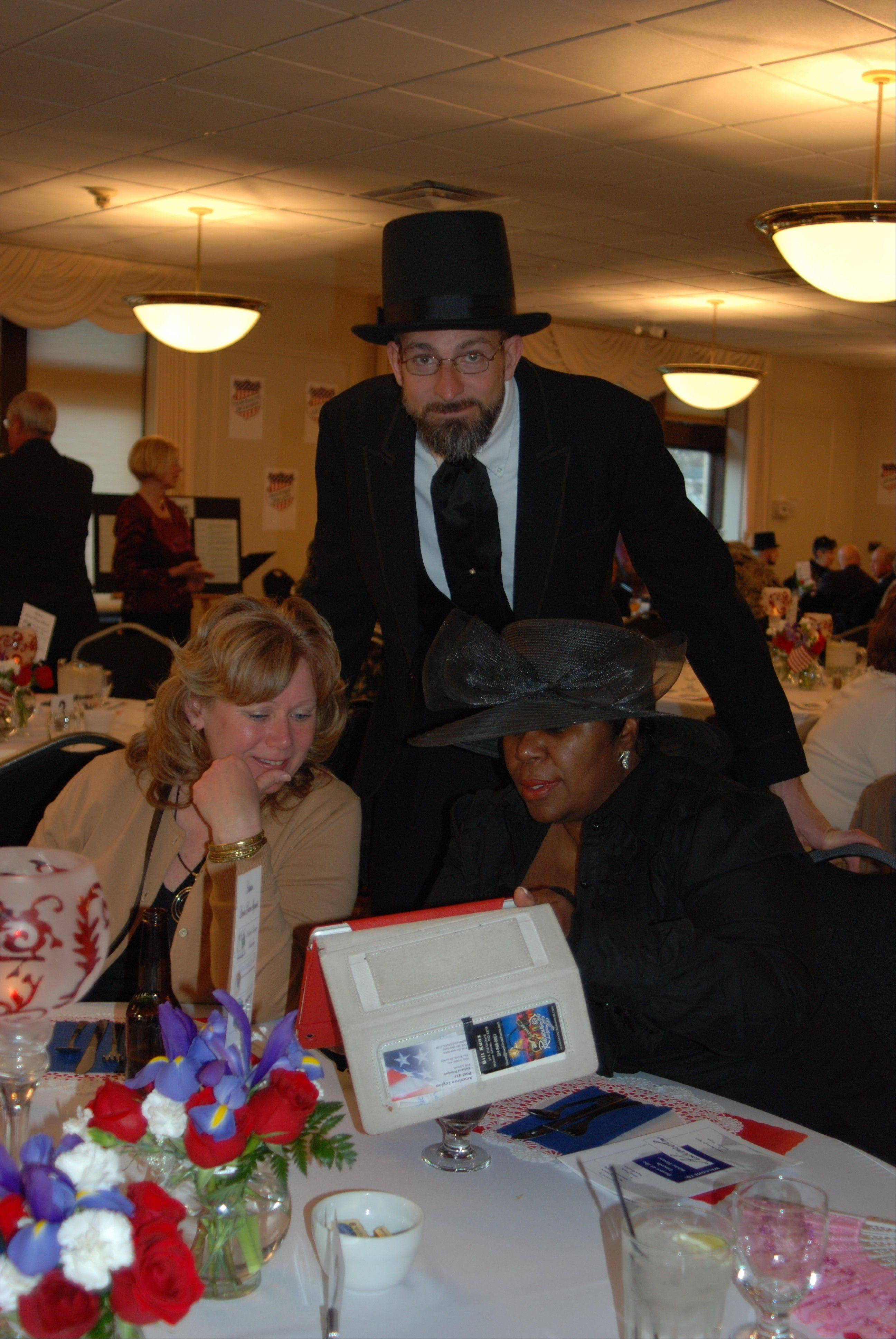 """Abe Lincoln,"" played by Tom Novack, visits with Mary Zander of Picket Fence Realty and Joann Smith during the April 20 ""History in the Headlines"" fundraiser."