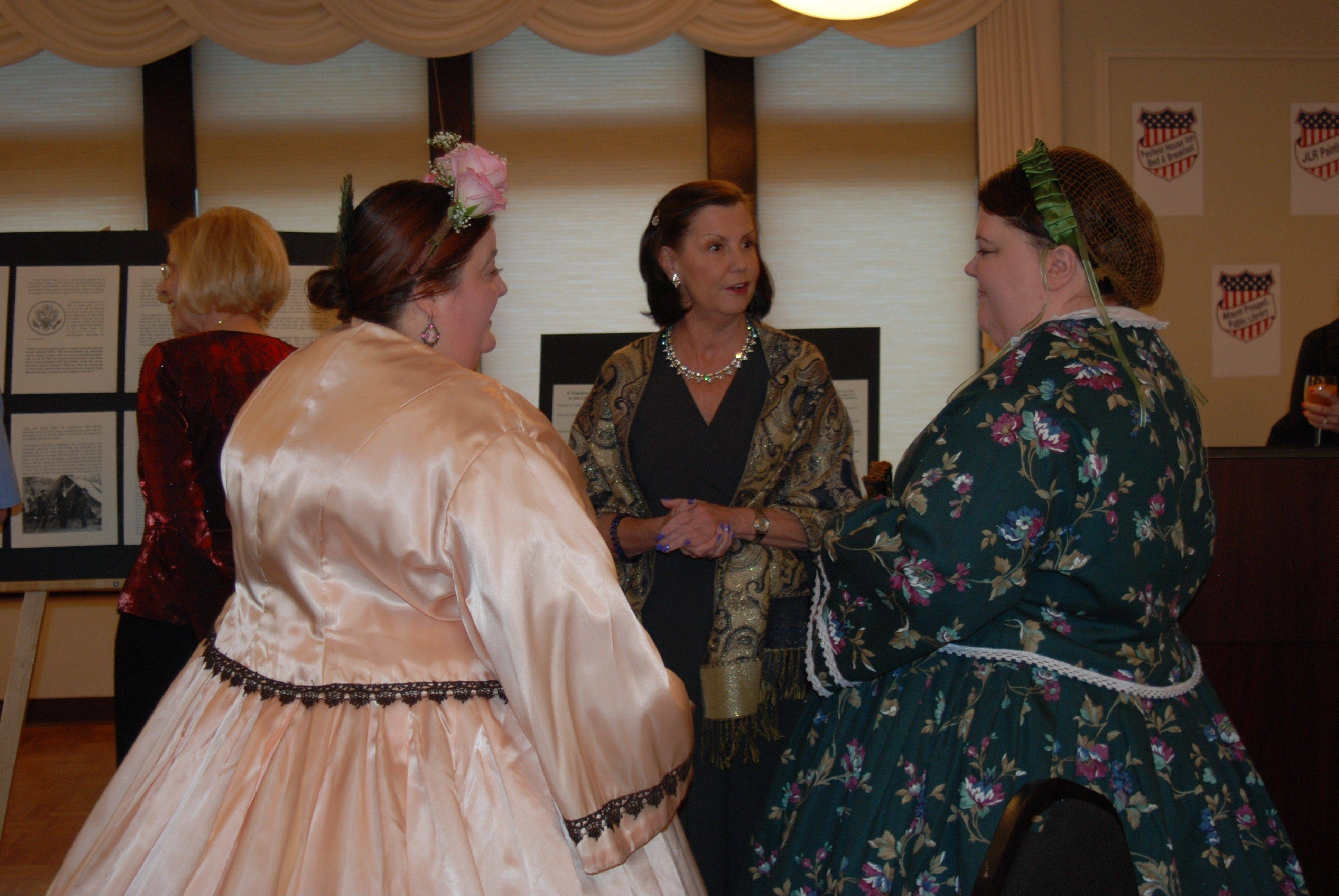 "Mary Bowman of Peterson Roofing converses with Mary Todd Lincoln and her Southern-sympathizing sister, Emilie Todd Helms, who presented the after-dinner program at the ""History in the Headlines"" fundraiser."