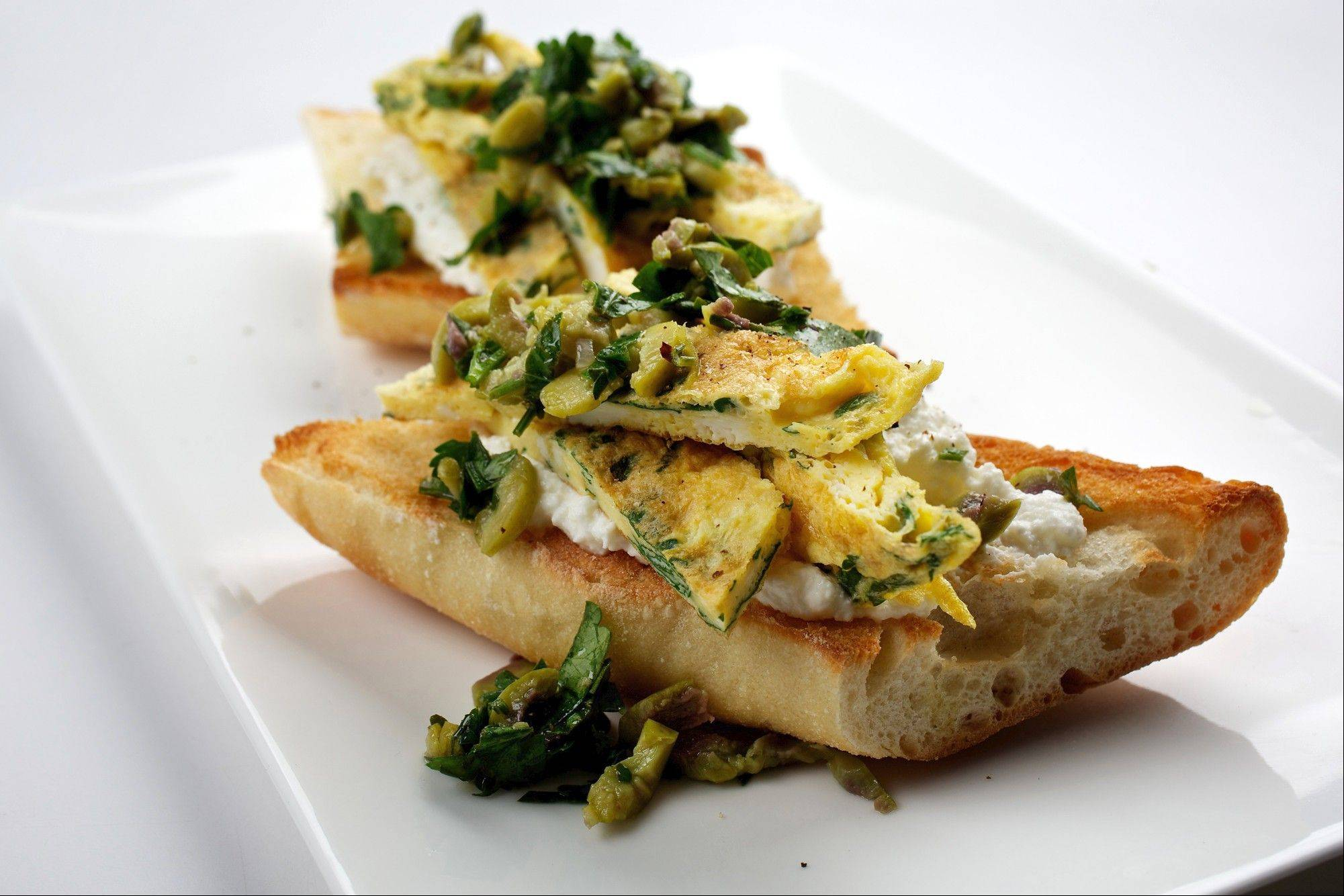 Parsley, olive, egg and ricotta come together nicely as a sandwich filling for a baguette. Or, forget the toast and enjoy it as an omelet.